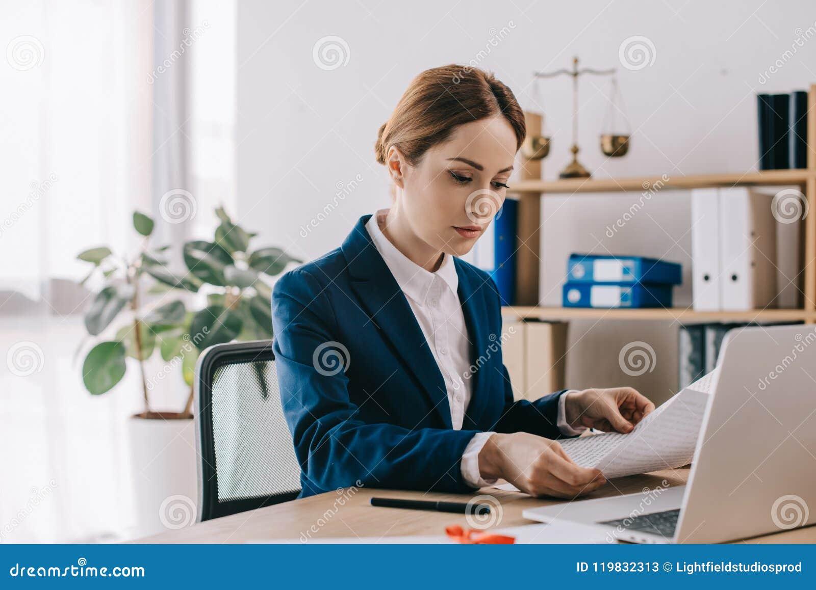 Boczny widok skoncentrowany żeński prawnik pracuje z dokumentami przy miejscem pracy