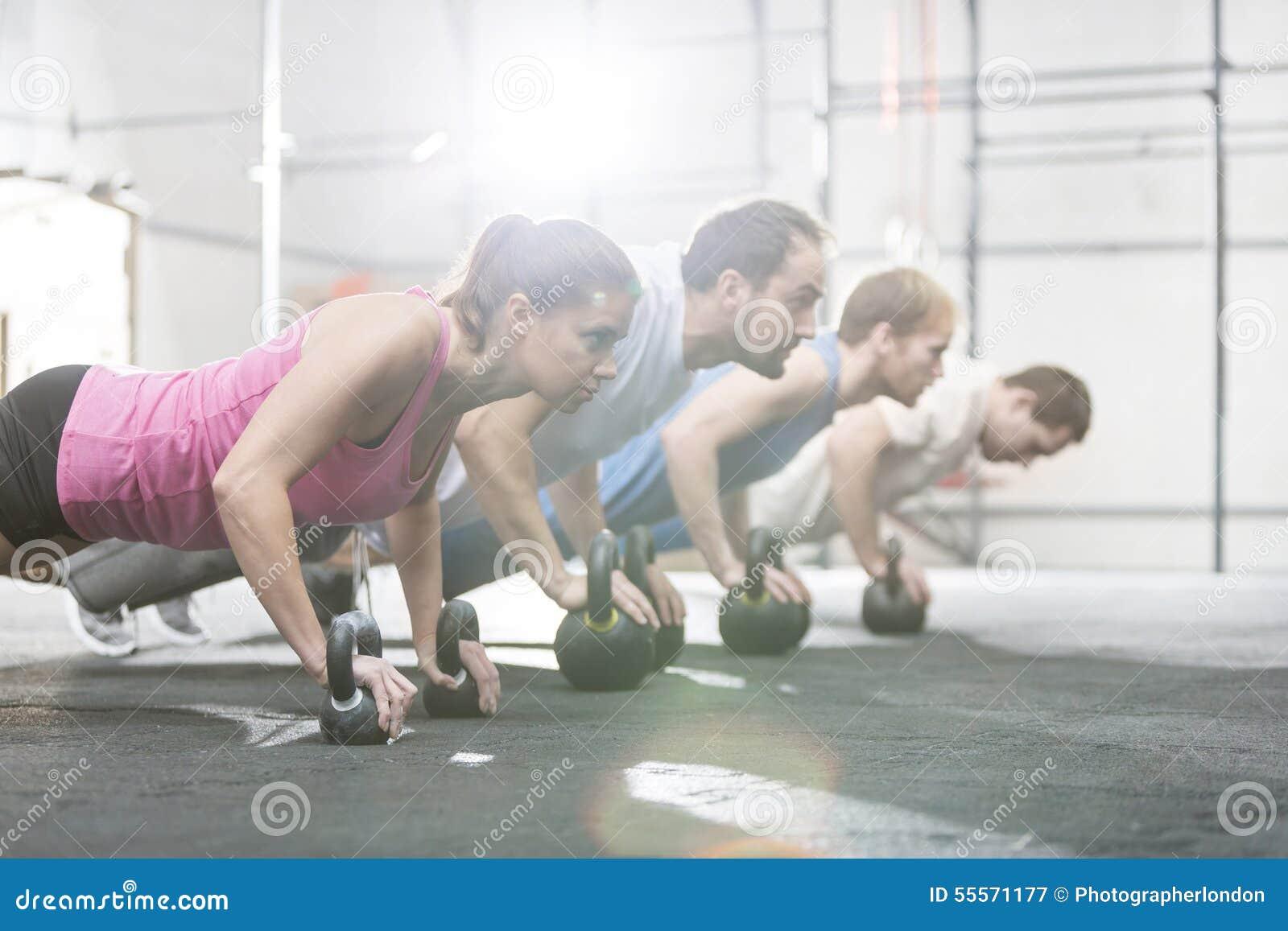 Boczny widok zdecydowani ludzie robi pushups z kettlebells przy crossfit gym