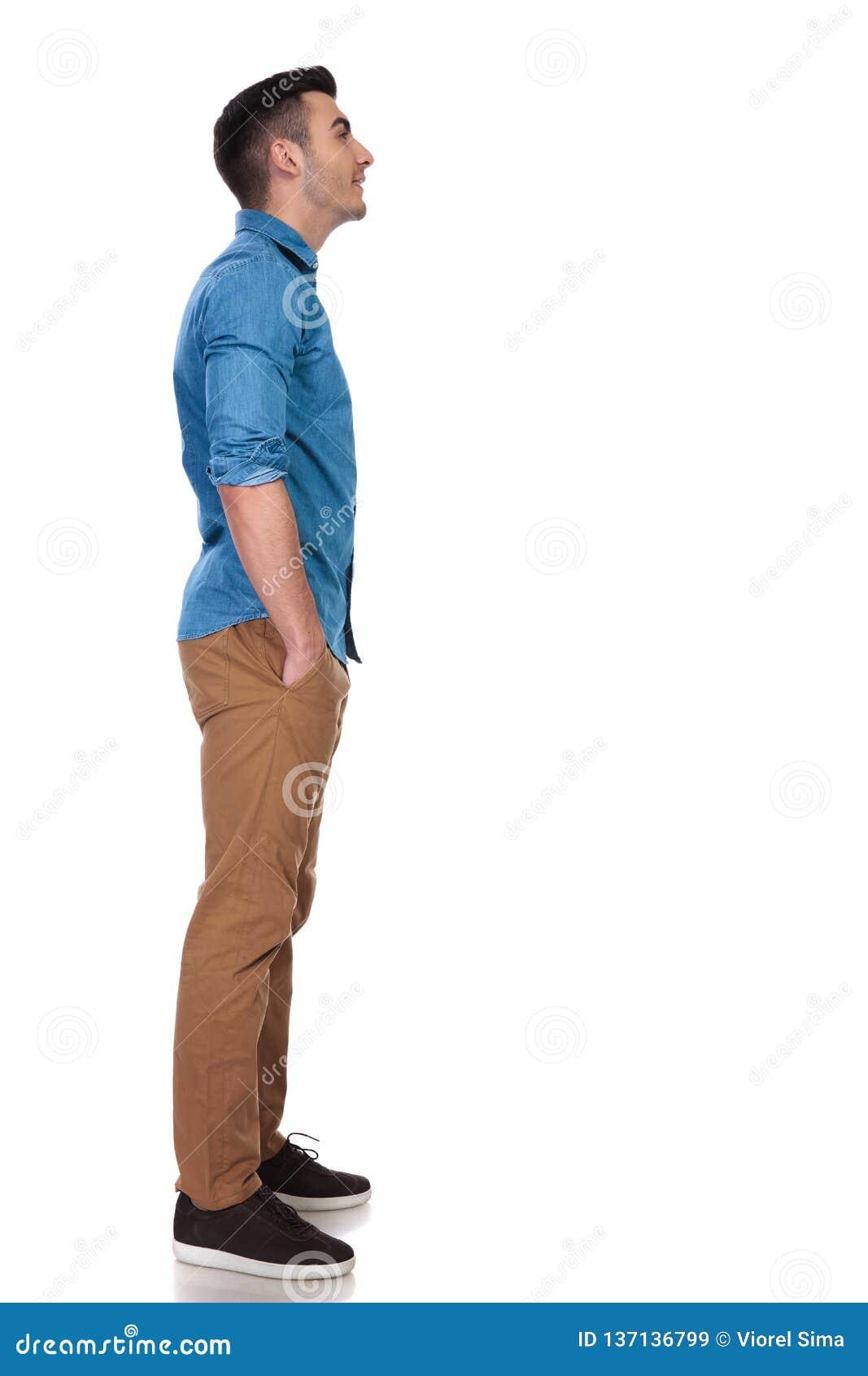 Boczny widok zrelaksowany przypadkowy mężczyzna przyglądający w górę coś przy