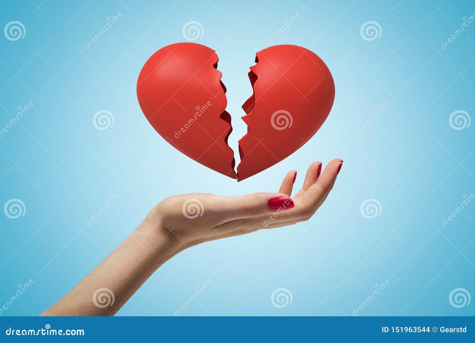 Boczny zbliżenie stawia czoło w górę kobiety ręka i levitating czerwony złamane serce na bławym gradientowym tle