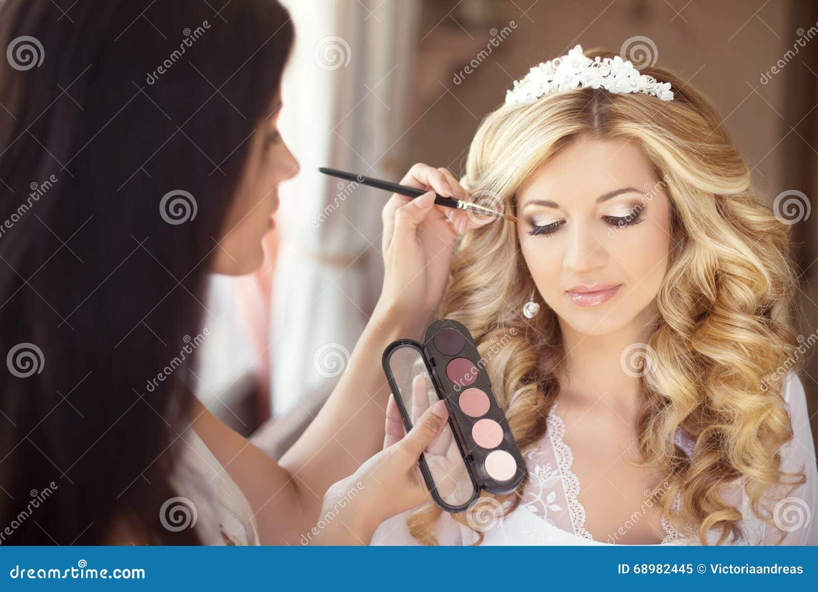Boda hermosa de la novia con maquillaje y el peinado rizado estilista