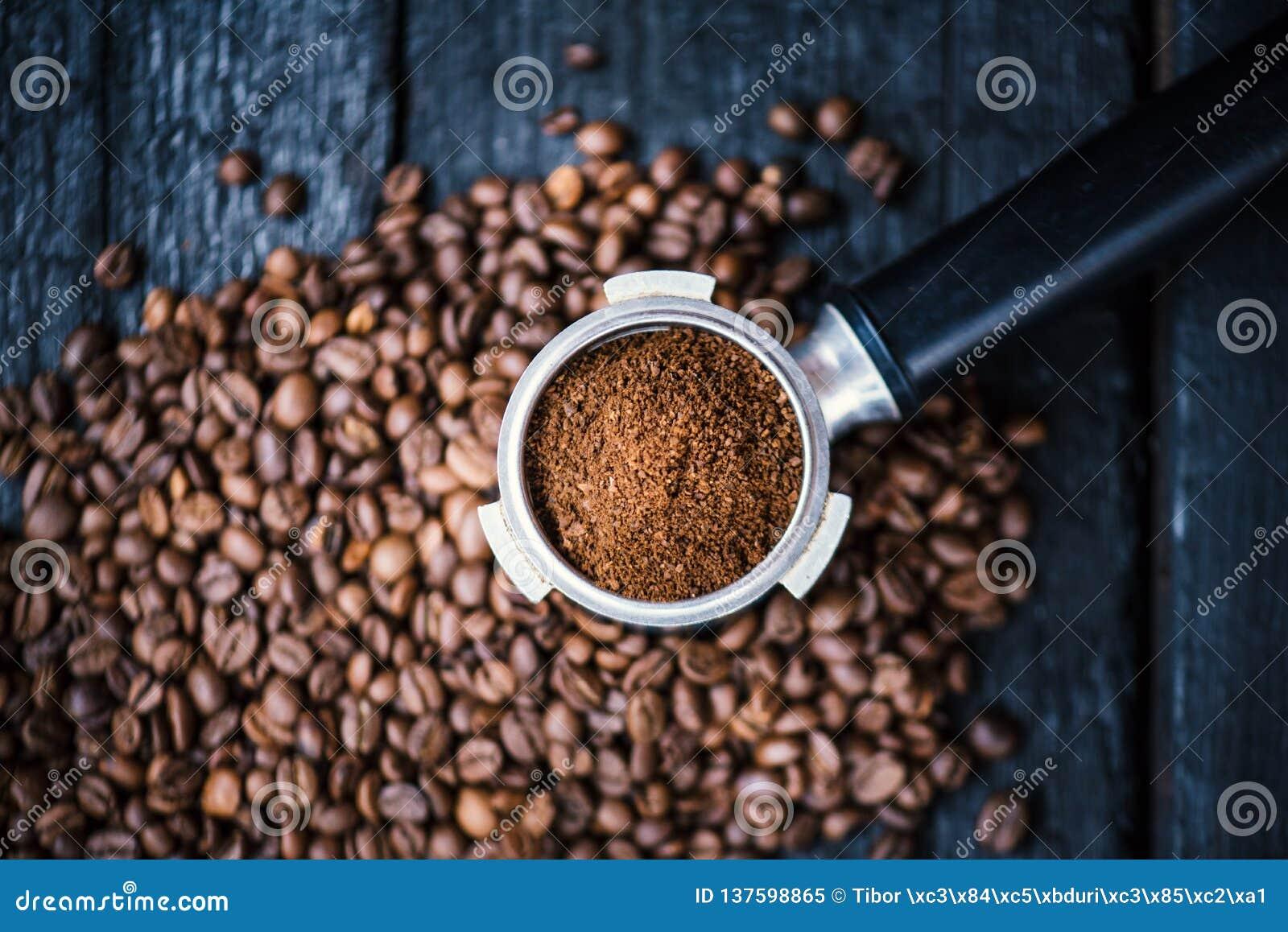 Bodemloze filter met malenbonen op een houten zwarte lijst De geroosterde Bonen van de Koffie Espressoextractie Tref van espresso
