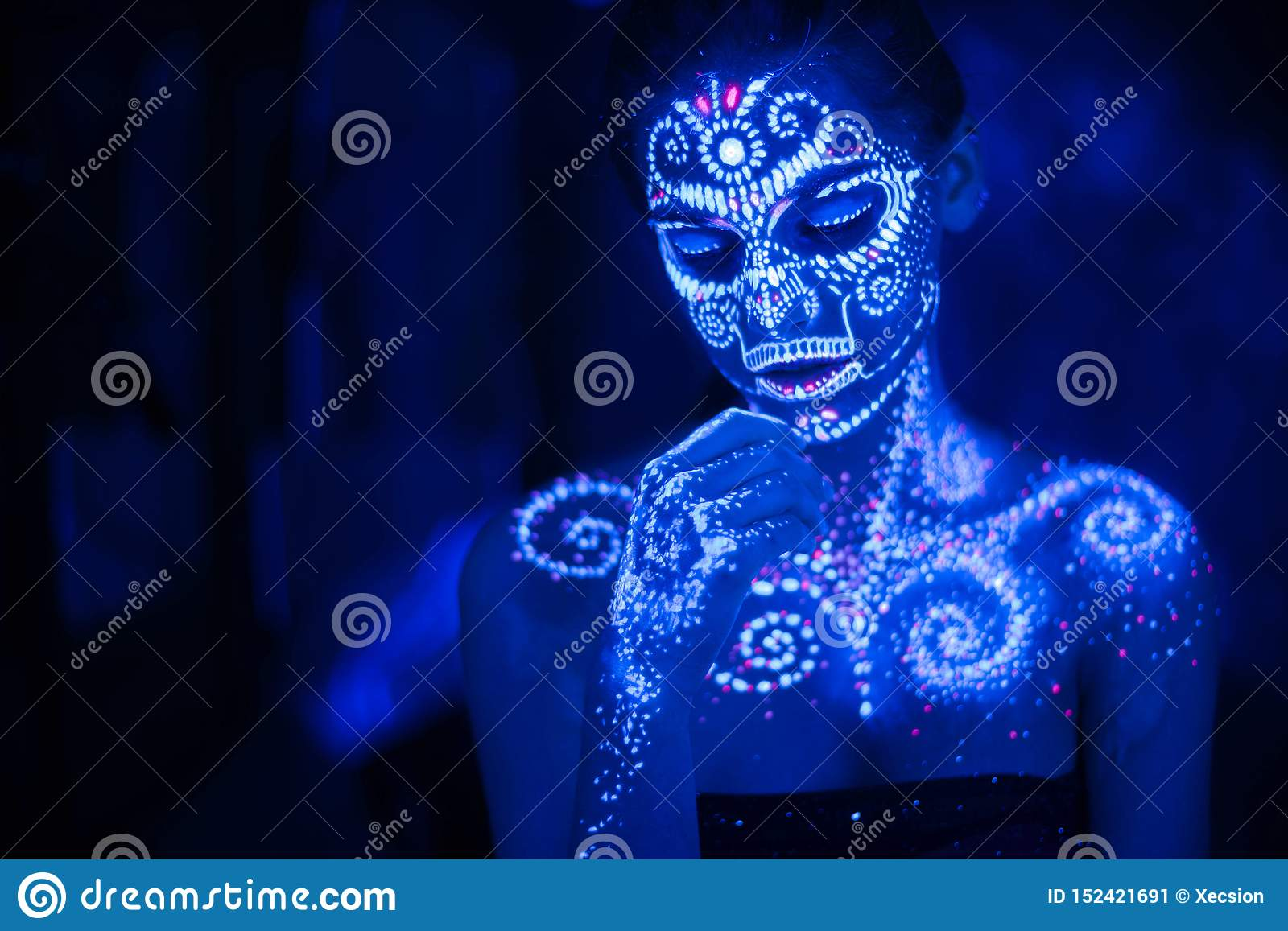 Body art on the body and hand of a girl glowing in the ultraviolet light