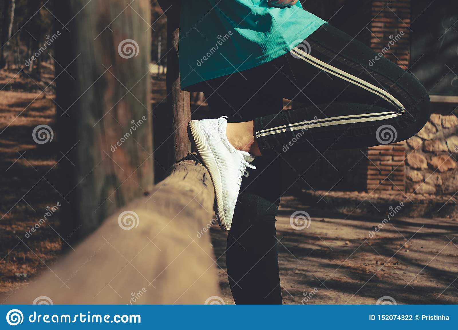 Horizontal capture of a woman resting in a wooden fence wearing sport clothes
