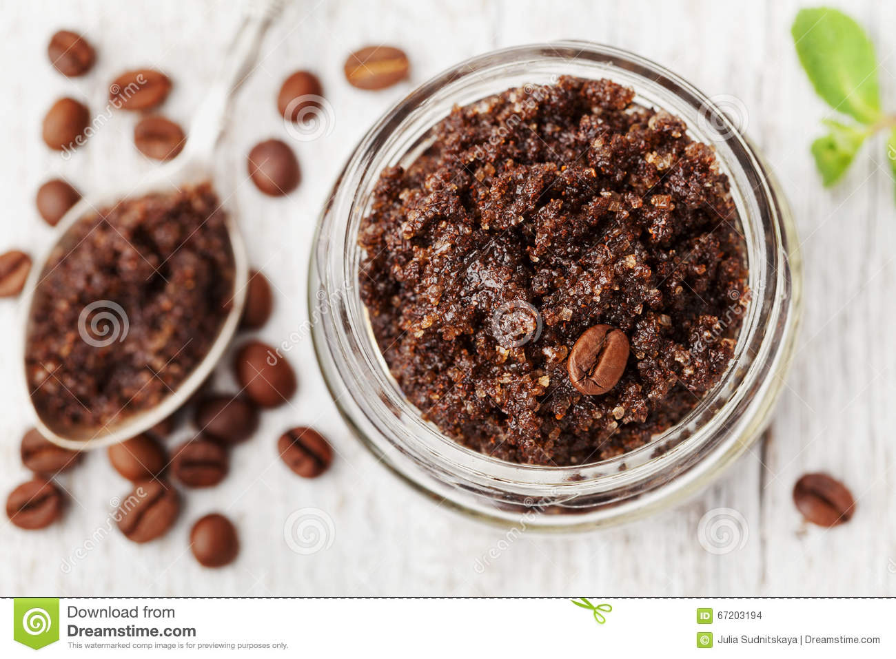 Body scrub of ground coffee, sugar and coconut oil in glass jar on white rustic table, homemade cosmetic for peeling and spa