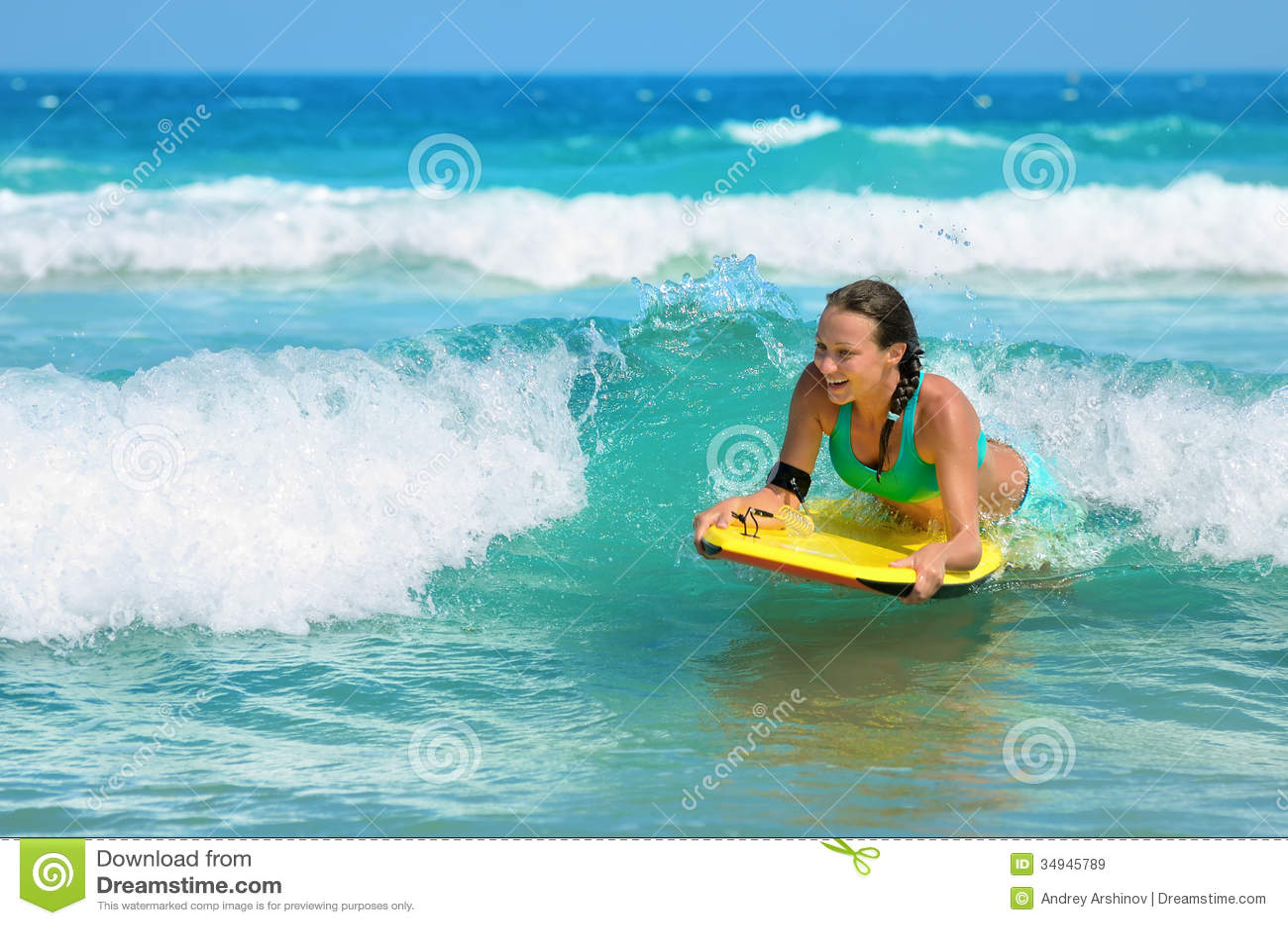 Bodyboards atractivos jovenes de la mujer en la tabla hawaiana con sonrisa agradable