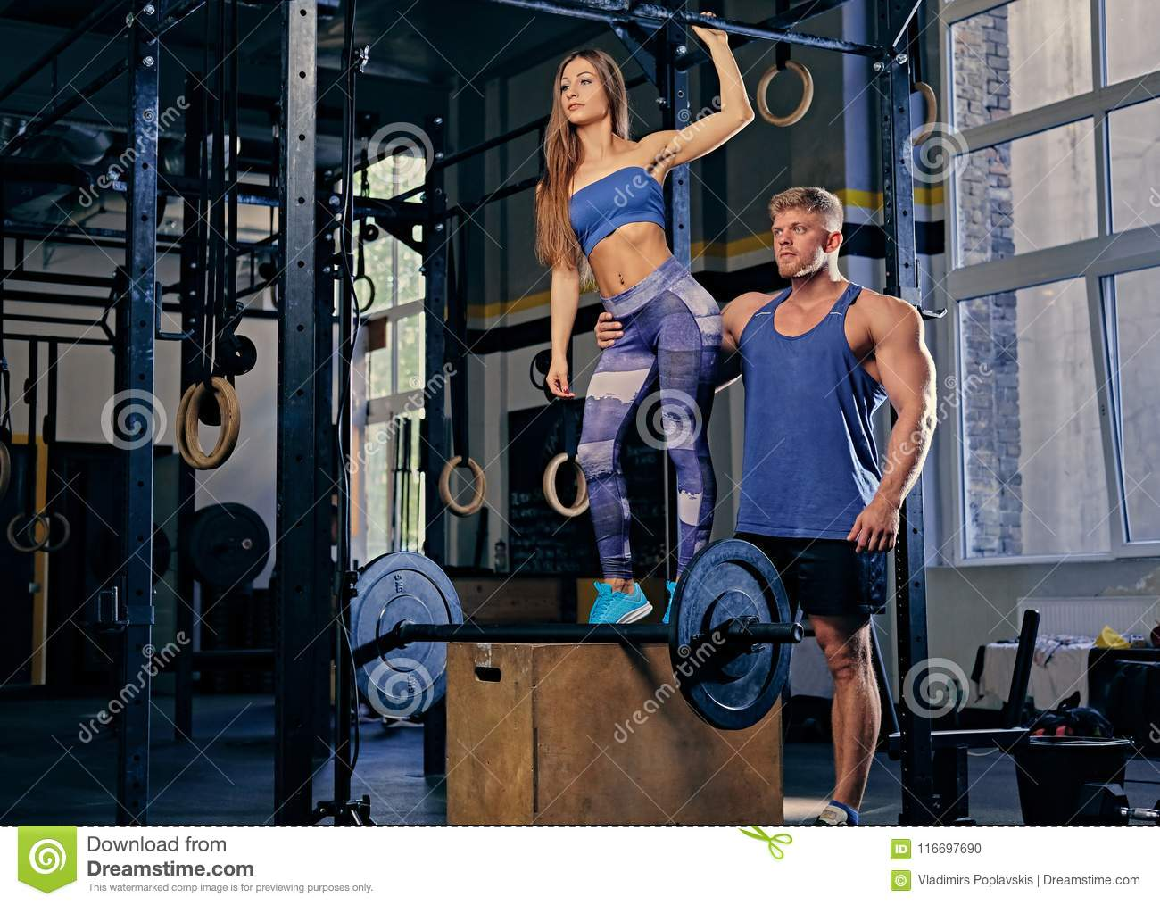 Bodybuilder Couple Posing On A Wooden Box In A Gym Club  Stock Photo