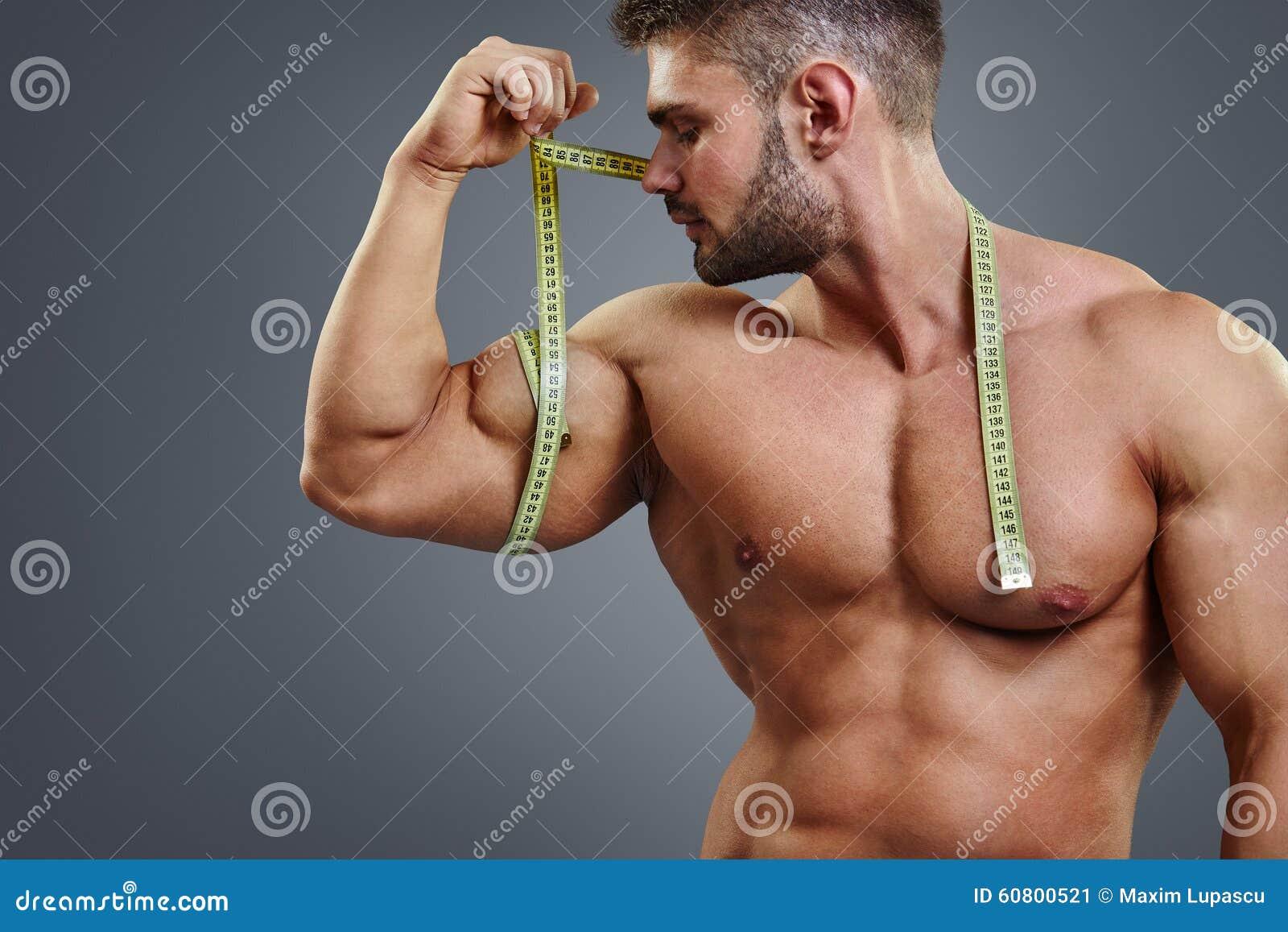 Bodybuilder die bicepsen met meetlint meten