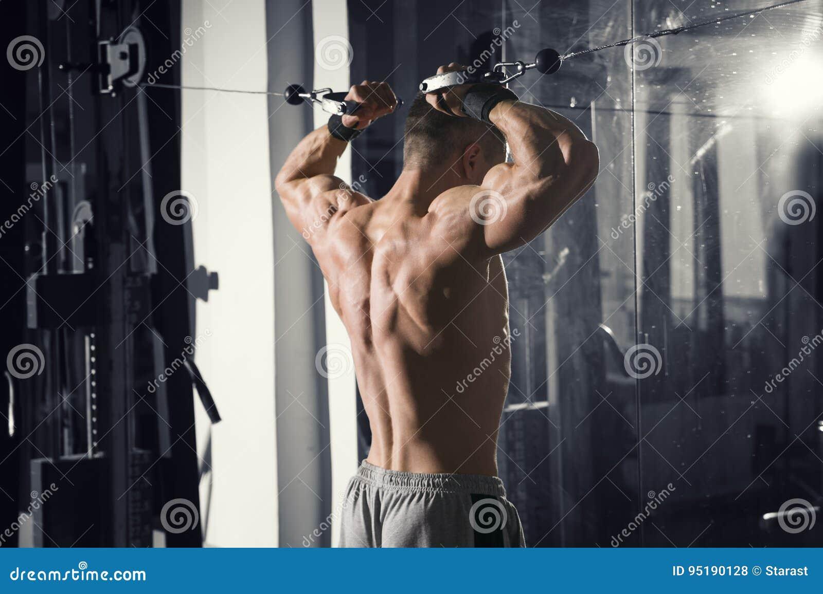 Bodybuilder trening na trenerze w gym, perfect mięśniowy męski ciało