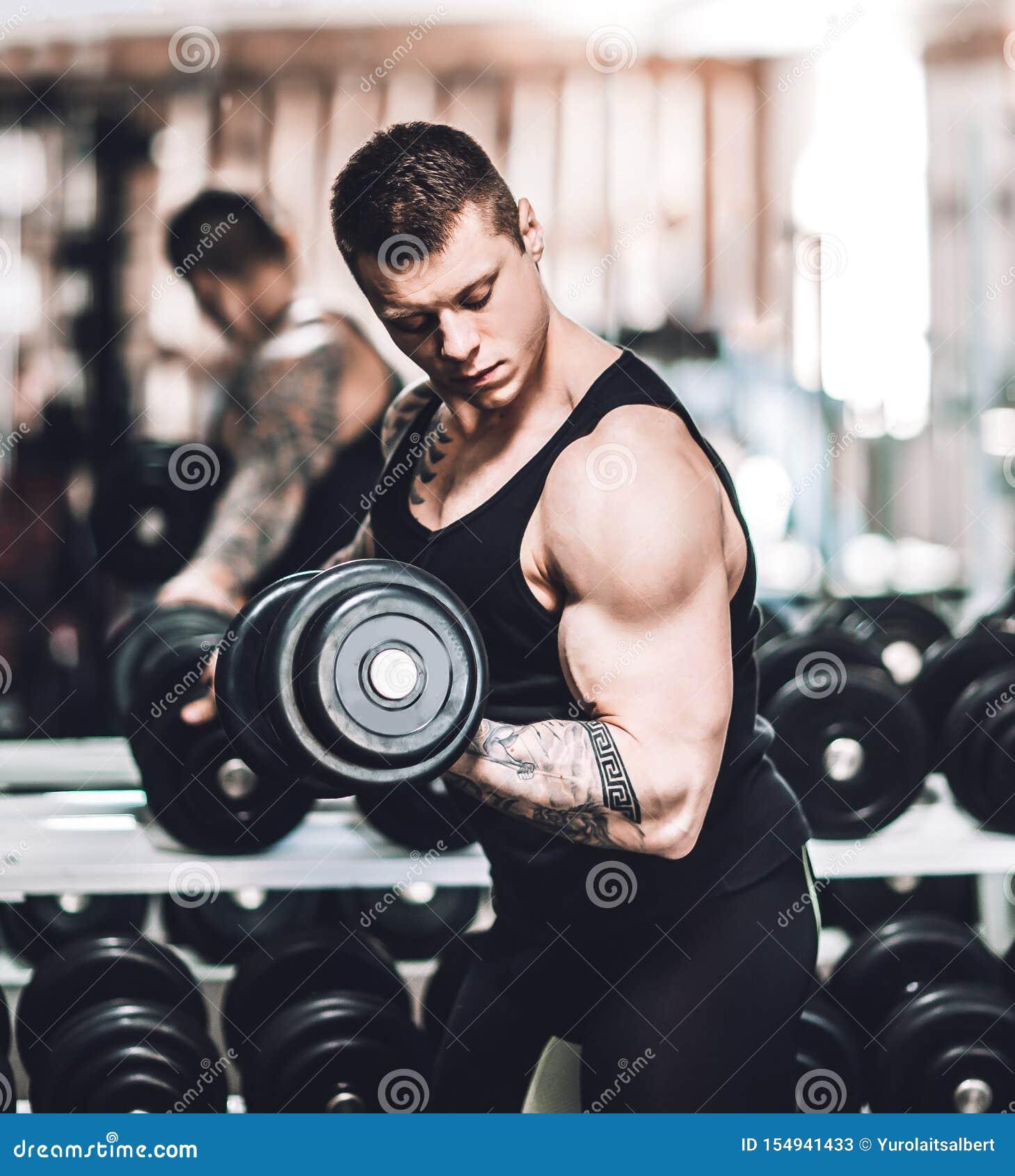 Bodybuilder wykonuje ćwiczenia z dumbbells Fotografia z kopii przestrzeni?