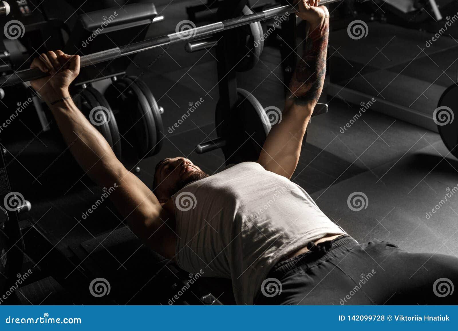 Bodybuilding Homem farpado que encontra-se fazendo a imprensa de banco no gym com o barbell concentrado