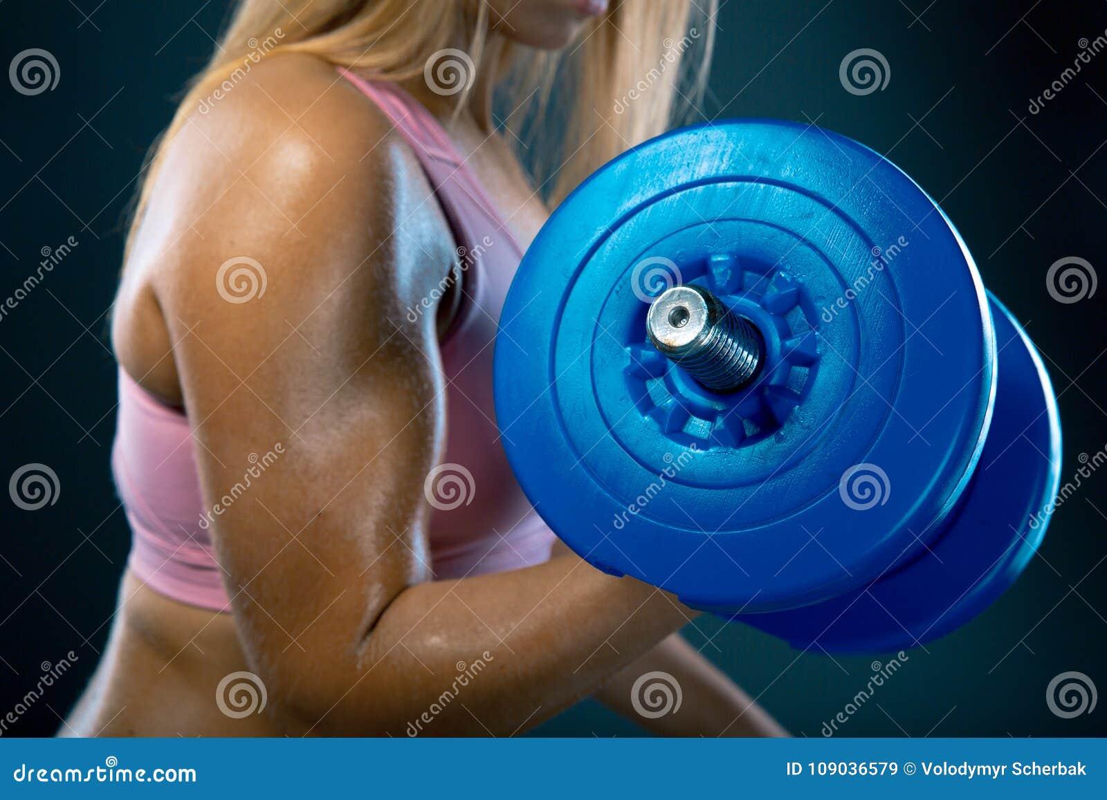 Bodybuilding Mulher forte do ajuste que exercita com pesos A menina loura muscular que levanta peso o estúdio disparou na obscuri