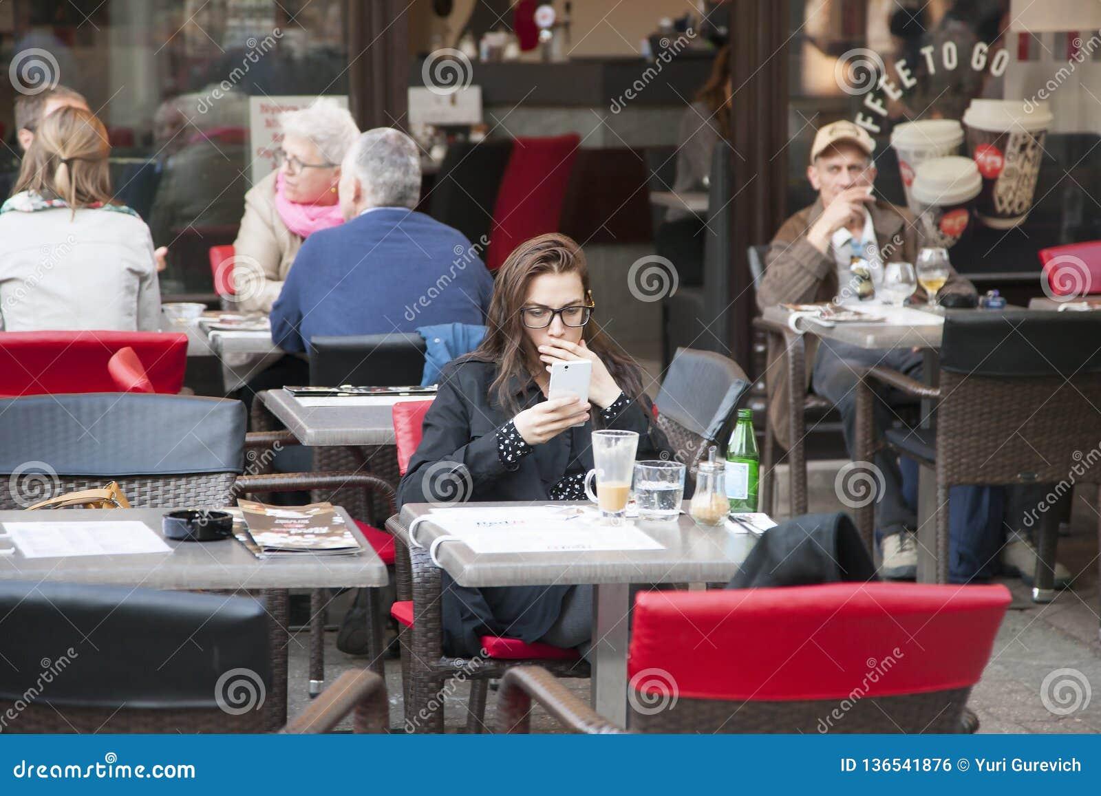 Boedapest, Hongarije - April 8, 2018: Het mooie meisje schrijft een sms-bericht op uw telefoon terwijl het zitten in koffiewinkel