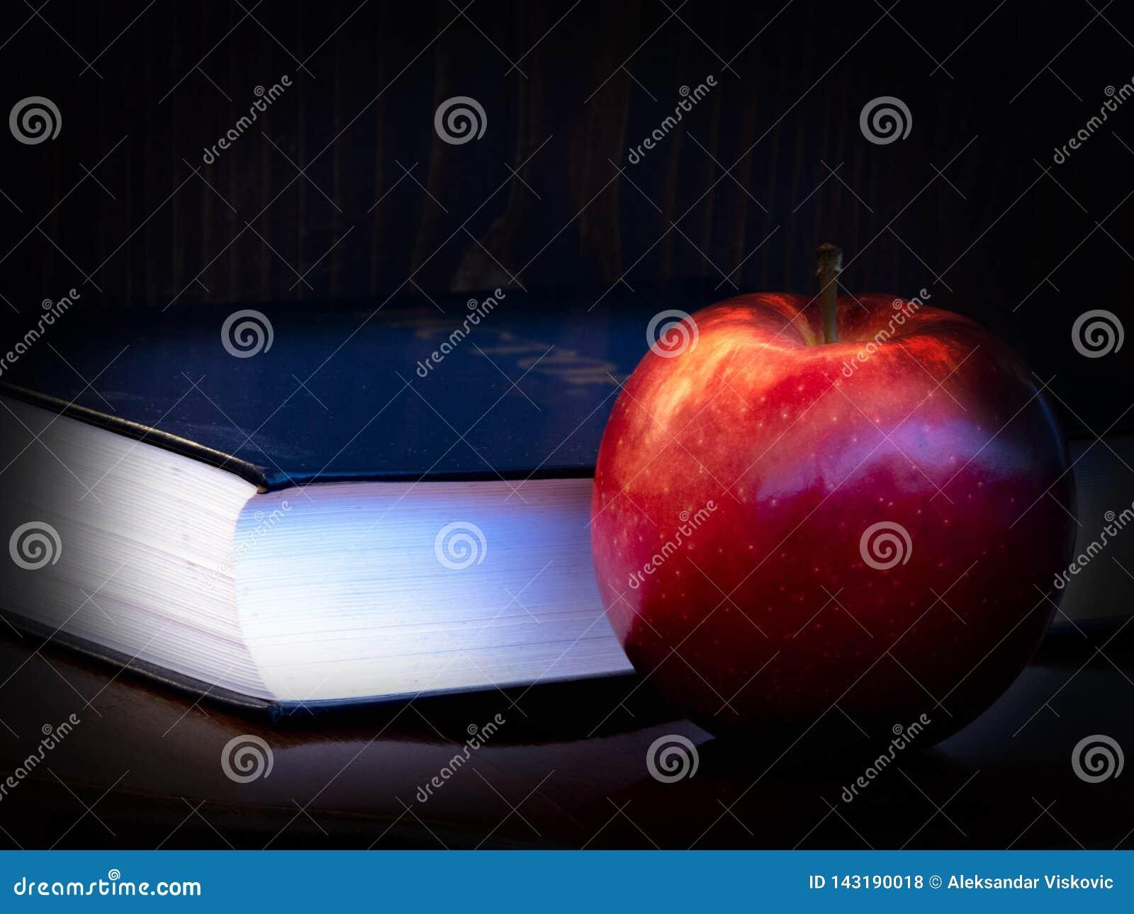 Boek en appel op donkere achtergrond