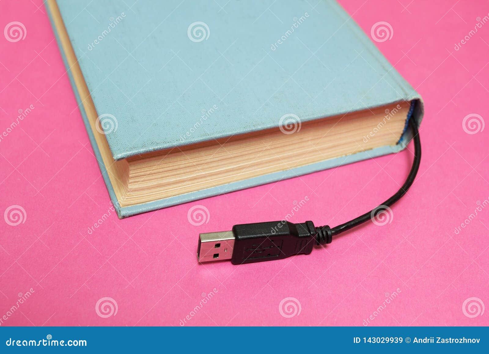 Boek met een schakelaar voor verbinding aan een computer op een roze achtergrond