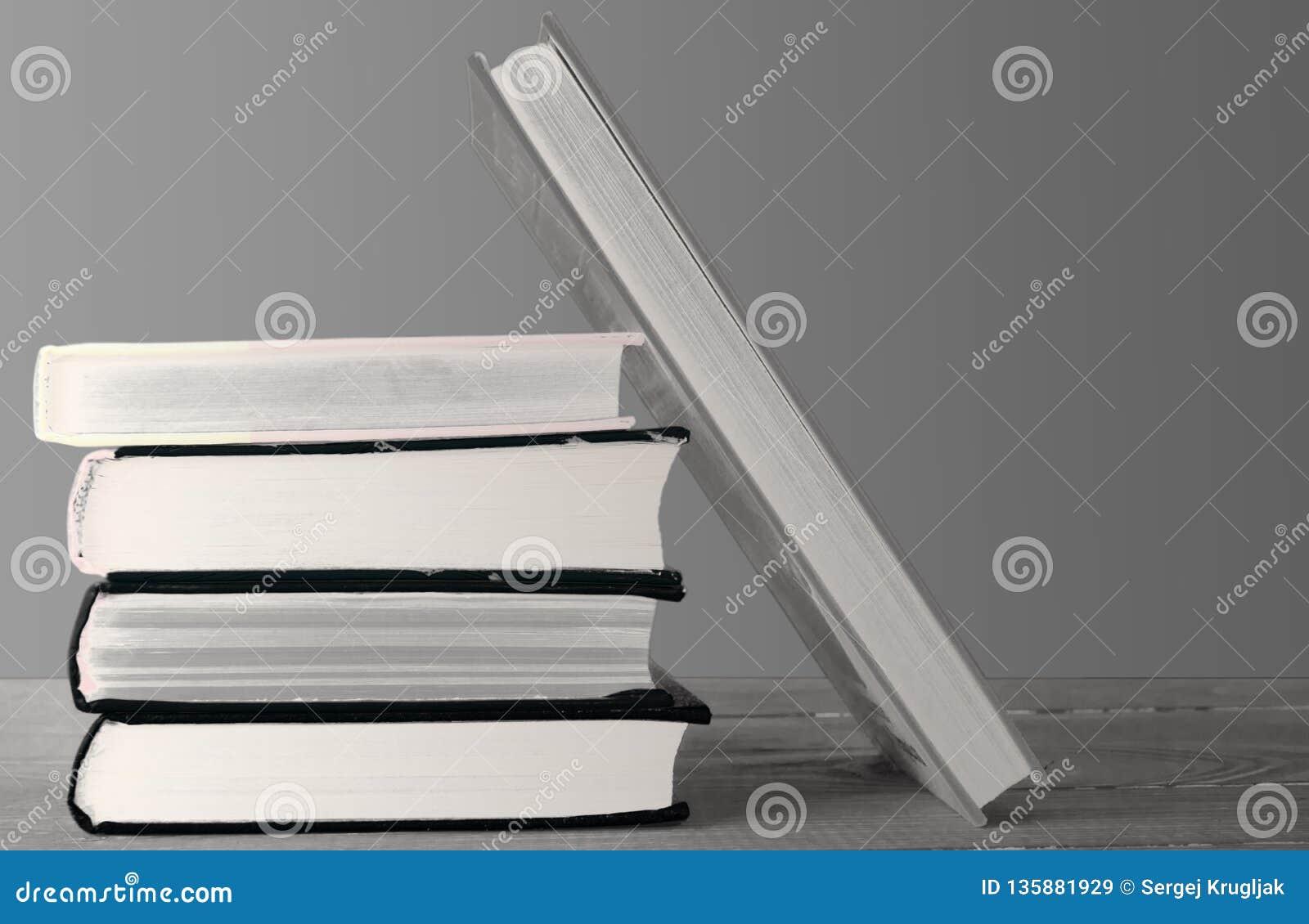 Boeken bovenop elkaar worden gestapeld die