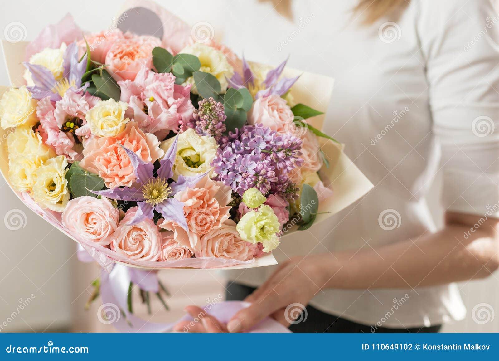 Boeket van gevoelige pastelkleur mooie luxebos van gemengde bloemen in de hand van de vrouw het werk van de bloemist bij a