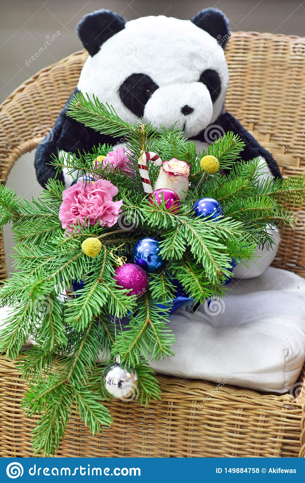 Boeket van Kerstboom met Kerstmisdecoratie en mooie bloemen Op een rieten stoel Het stuk speelgoed draagt op de achtergrond