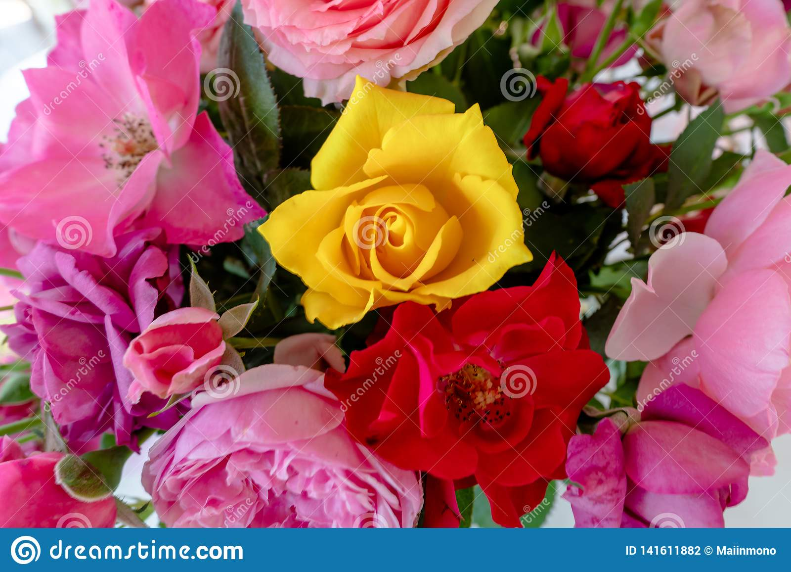 Boeket van kleurrijke gele, roze en rode rozen in een vaas