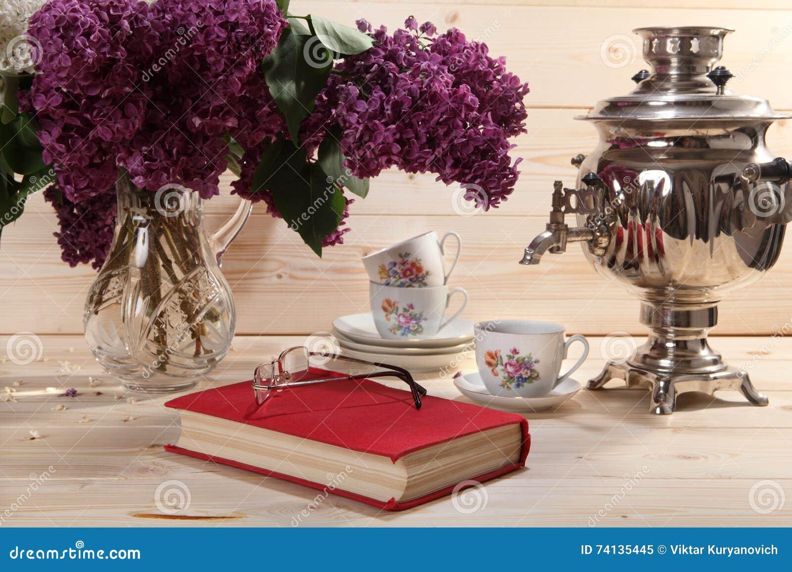 Boeket van seringen, samovar, kop thee, boek en bril
