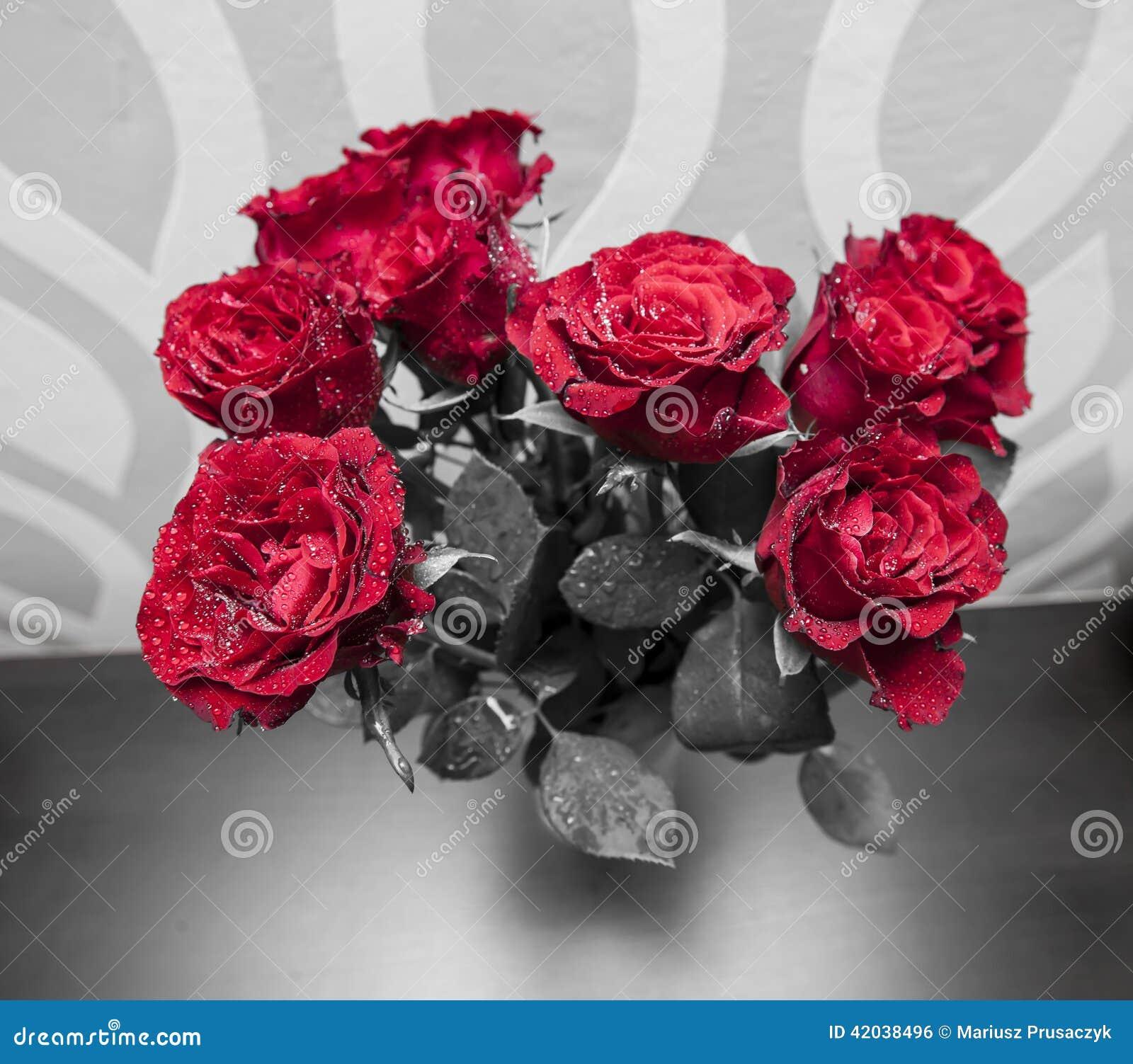 Boeket van tot bloei komende donkerrode rozen in vaas