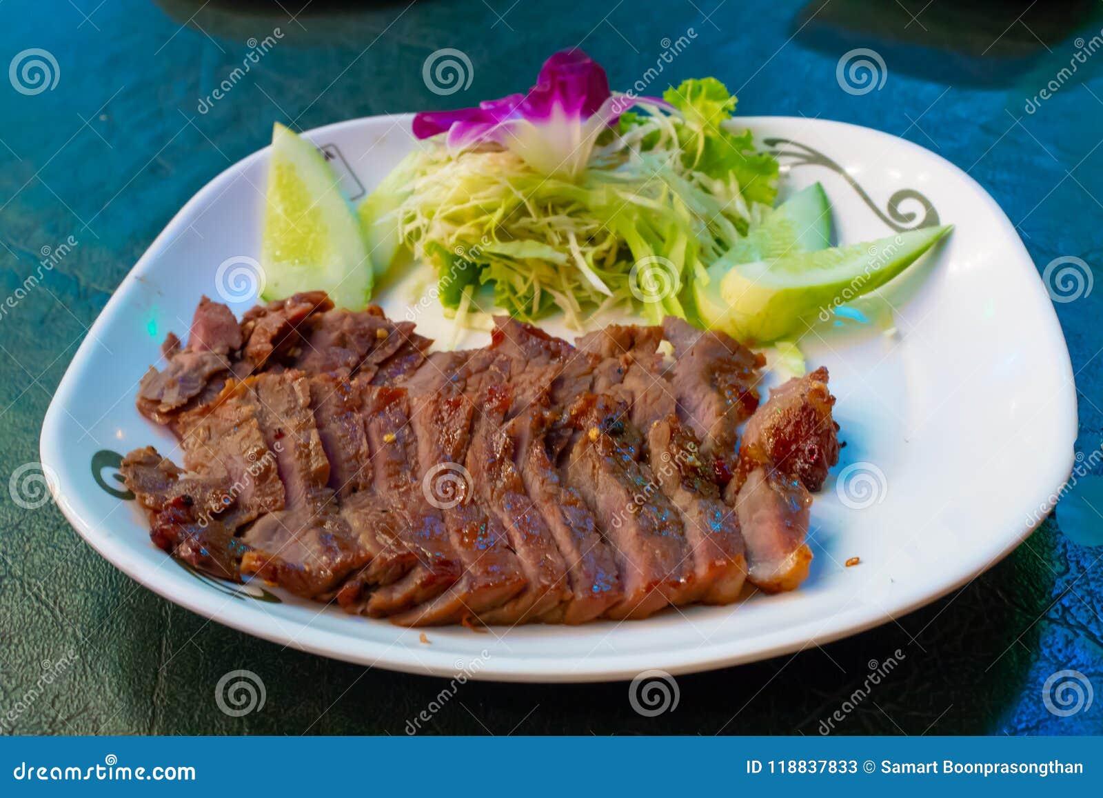 Boeuf grillé d un plat blanc avec de la sauce et les légumes