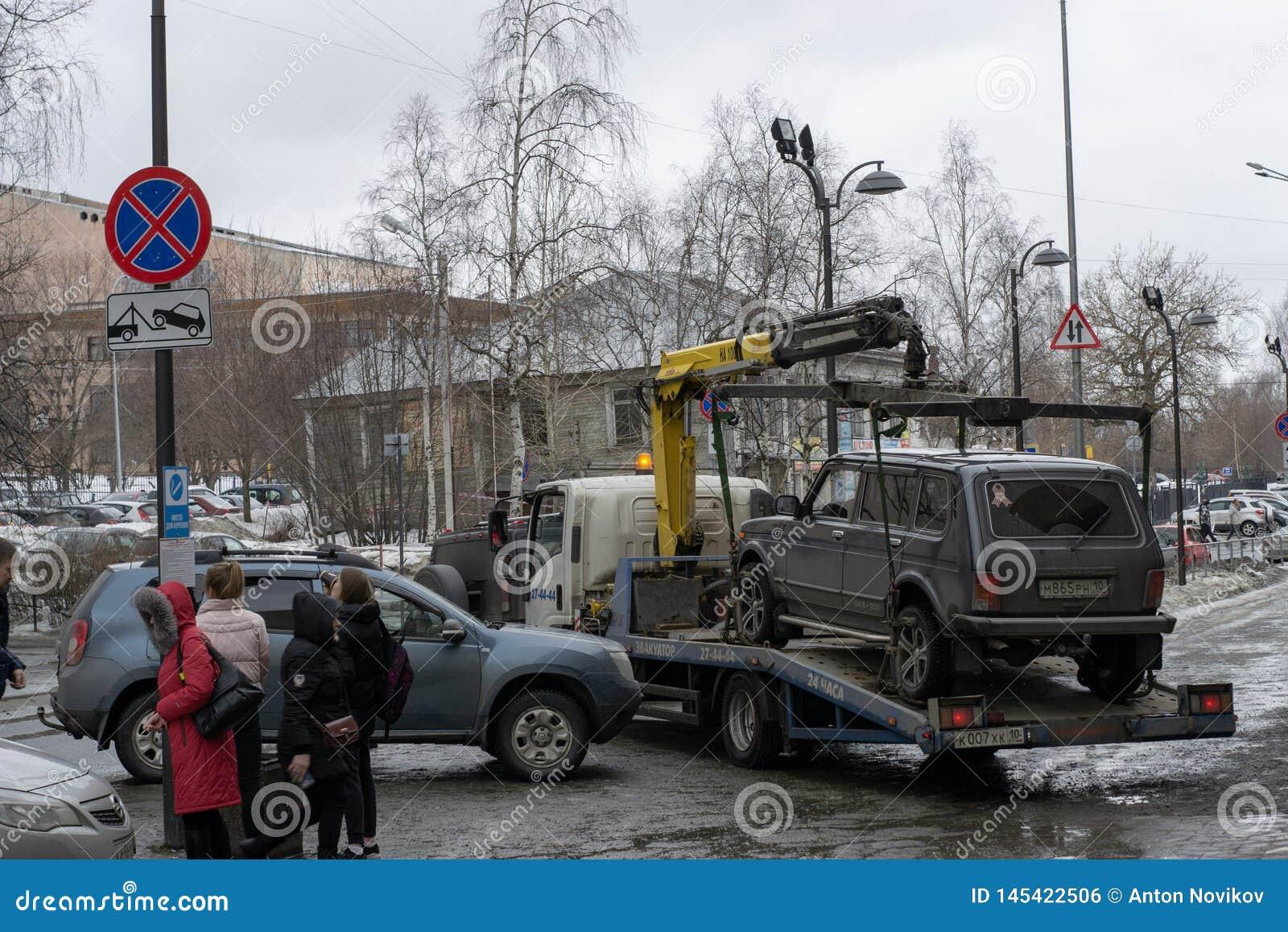 Bogsera av den olagligt parkerade bilen som har överträdt lokal trafik och parkeralagar