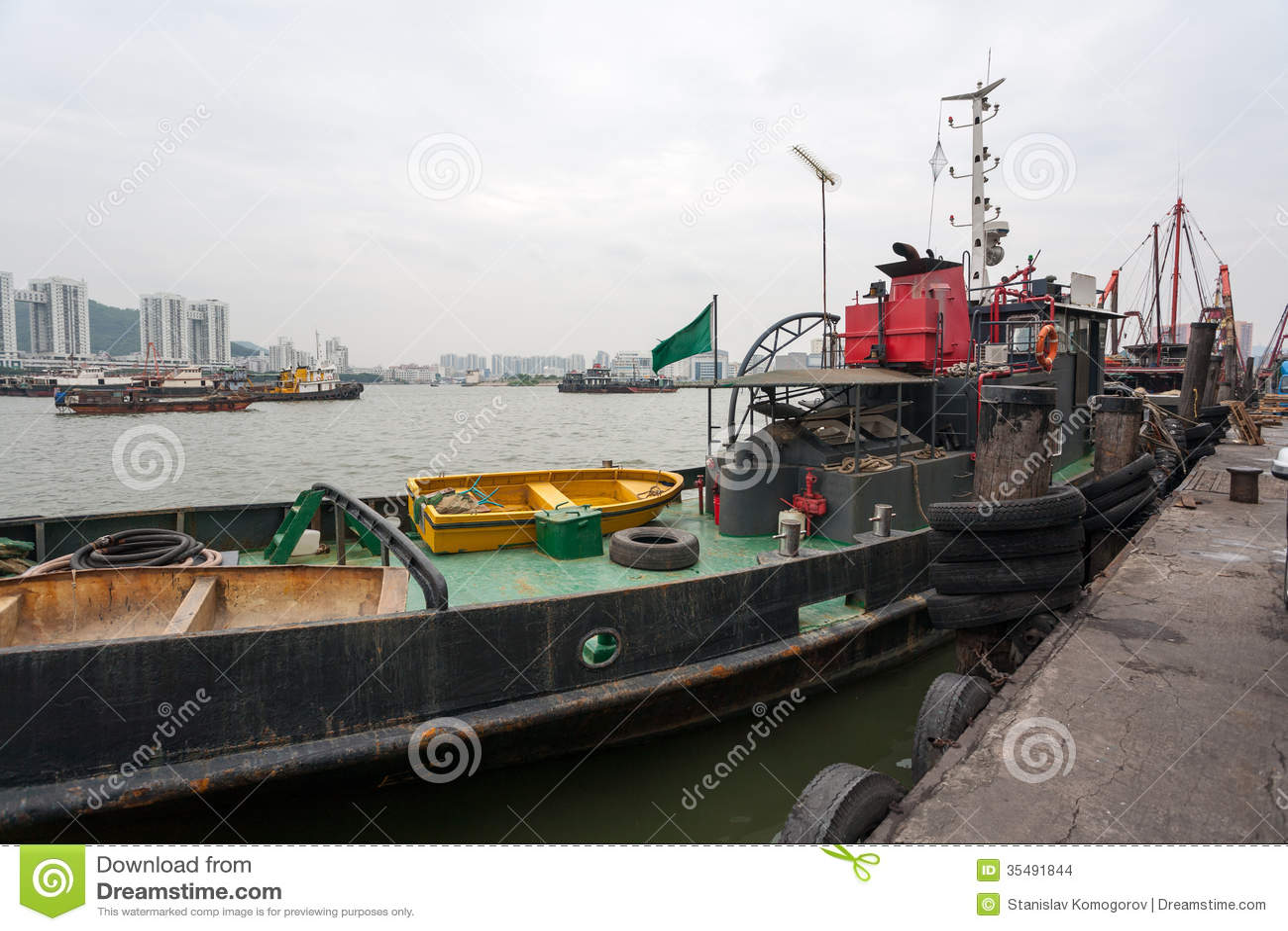 Bogserbåten och fiskeskyttlar är på hytten i porten av Macao.