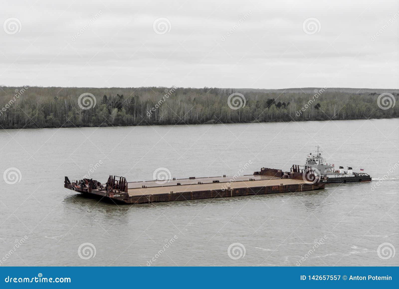 Bogserbåten skjuter pråm upp floden