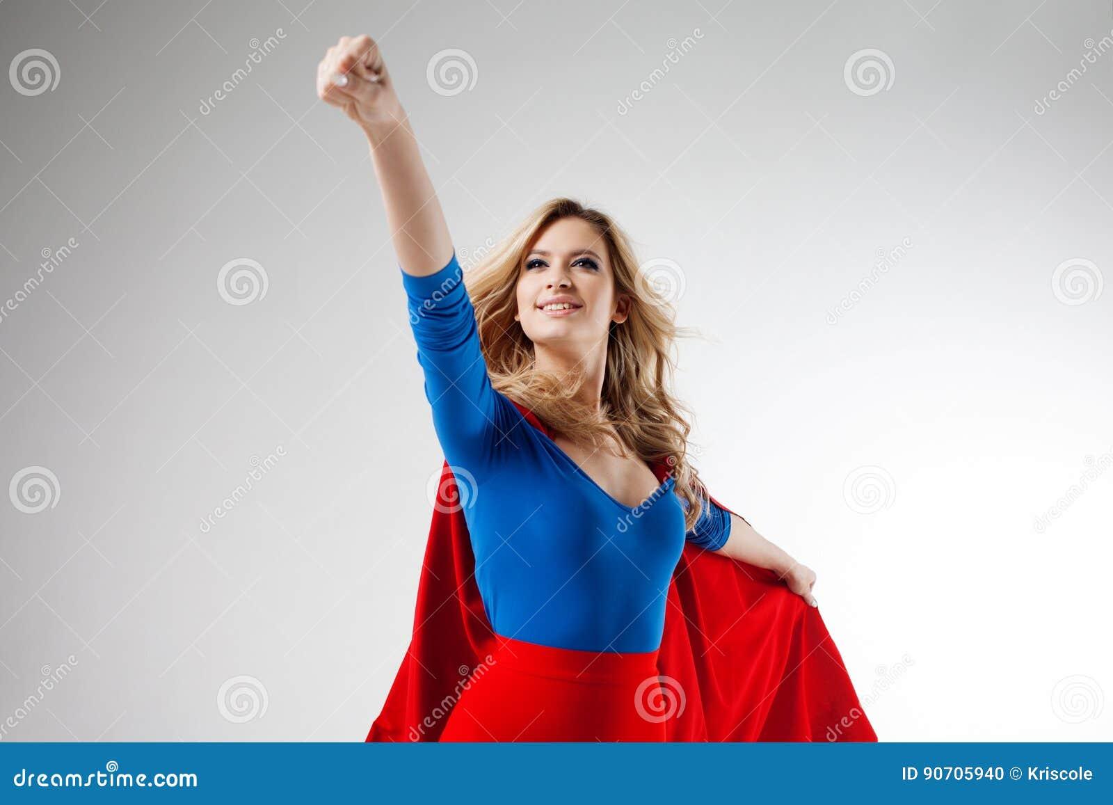 Bohater kobieta Młoda i piękna blondynka w wizerunku superheroine w czerwonym przylądka dorośnięciu Dalszy i oddolny