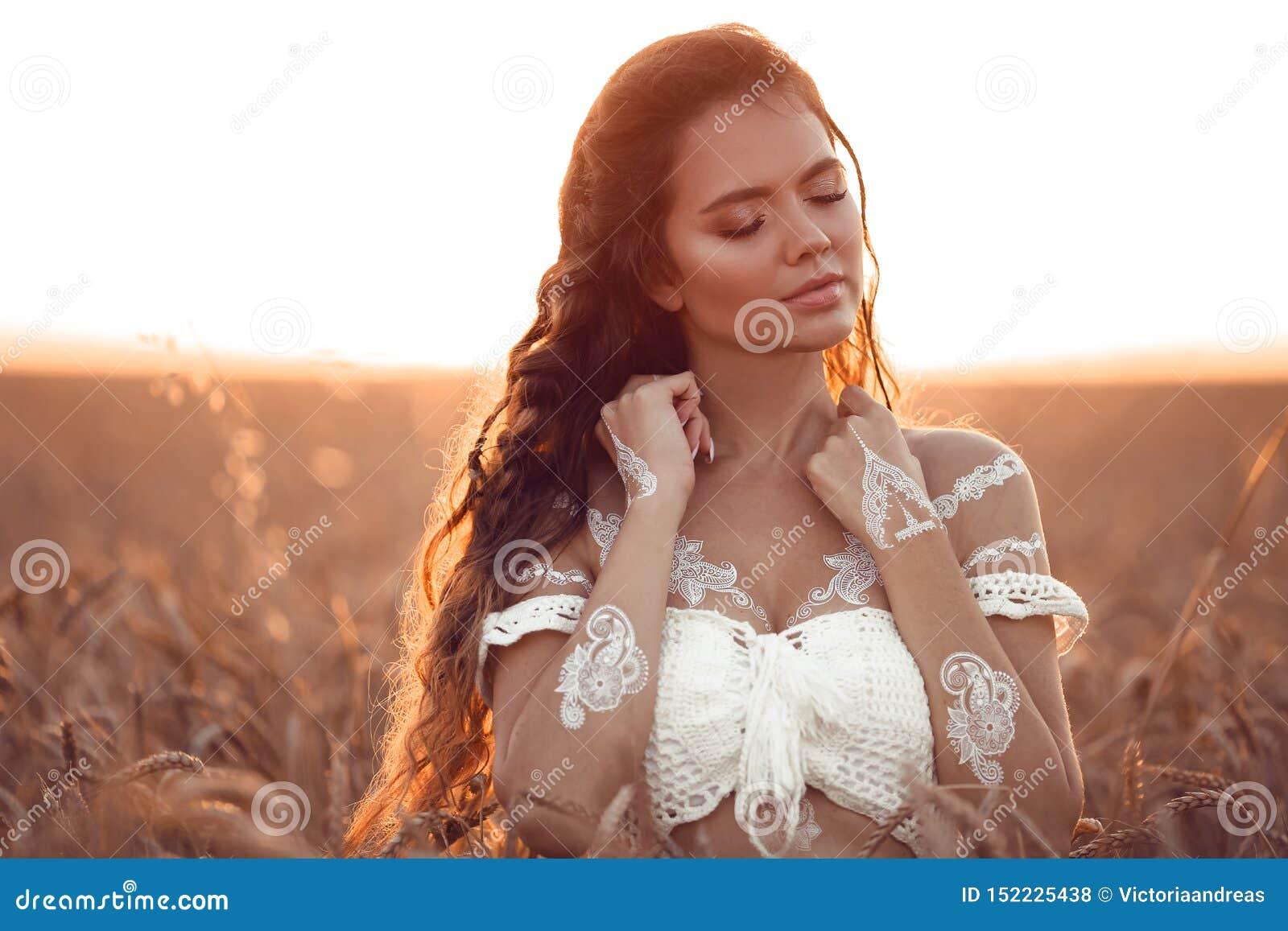 Boho chic stil Stående av den bohemiska flickan med vit konst som poserar över vetefält som tycker om på solnedgången Utomhus fot