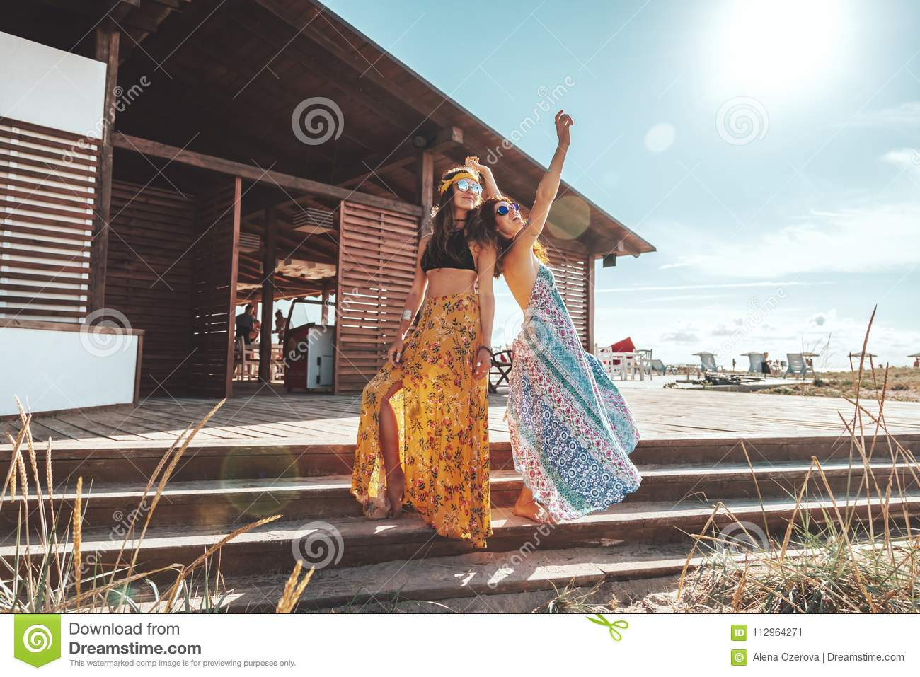 612eb414e3 Two boho friends girls wearing floral maxi dress and skirt relaxing on the  beach. Bohemian clothing style.