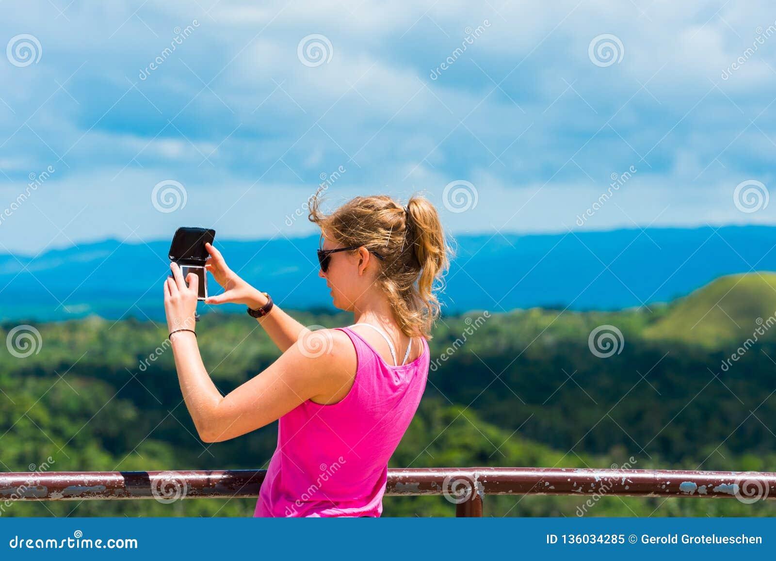 BOHOL, ФИЛИППИНЫ - 23-ЬЕ ФЕВРАЛЯ 2018: Девушка с камерой на предпосылке холмов шоколада фокуса съемка outdoors селективная