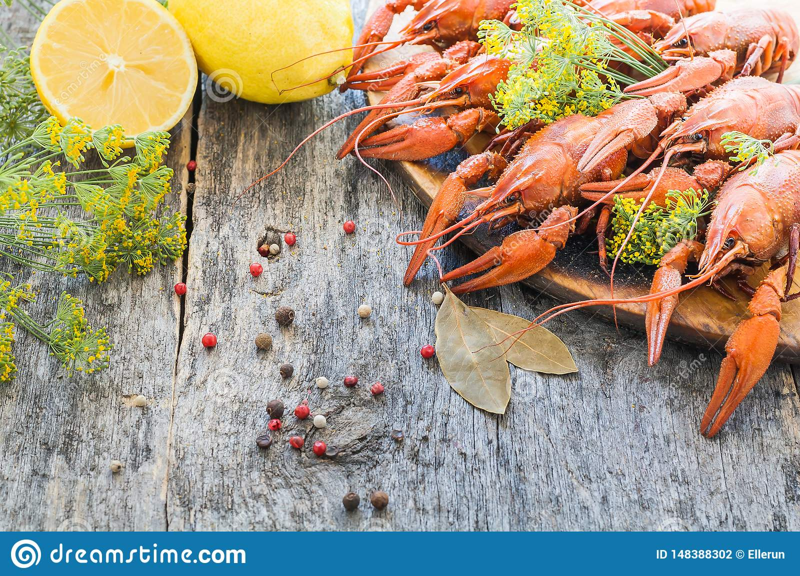 Boiled crawfish with lemon and dill on a wooden background