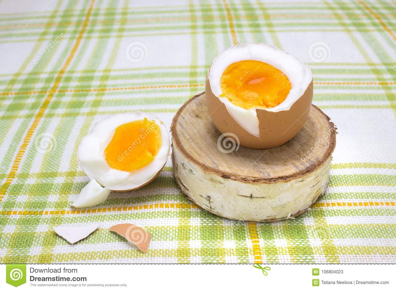 Boiled fresh egg for the breakfast on the wooden birch stand for eggs. Broken beige hen egg and pieces of shells, bright orange yo