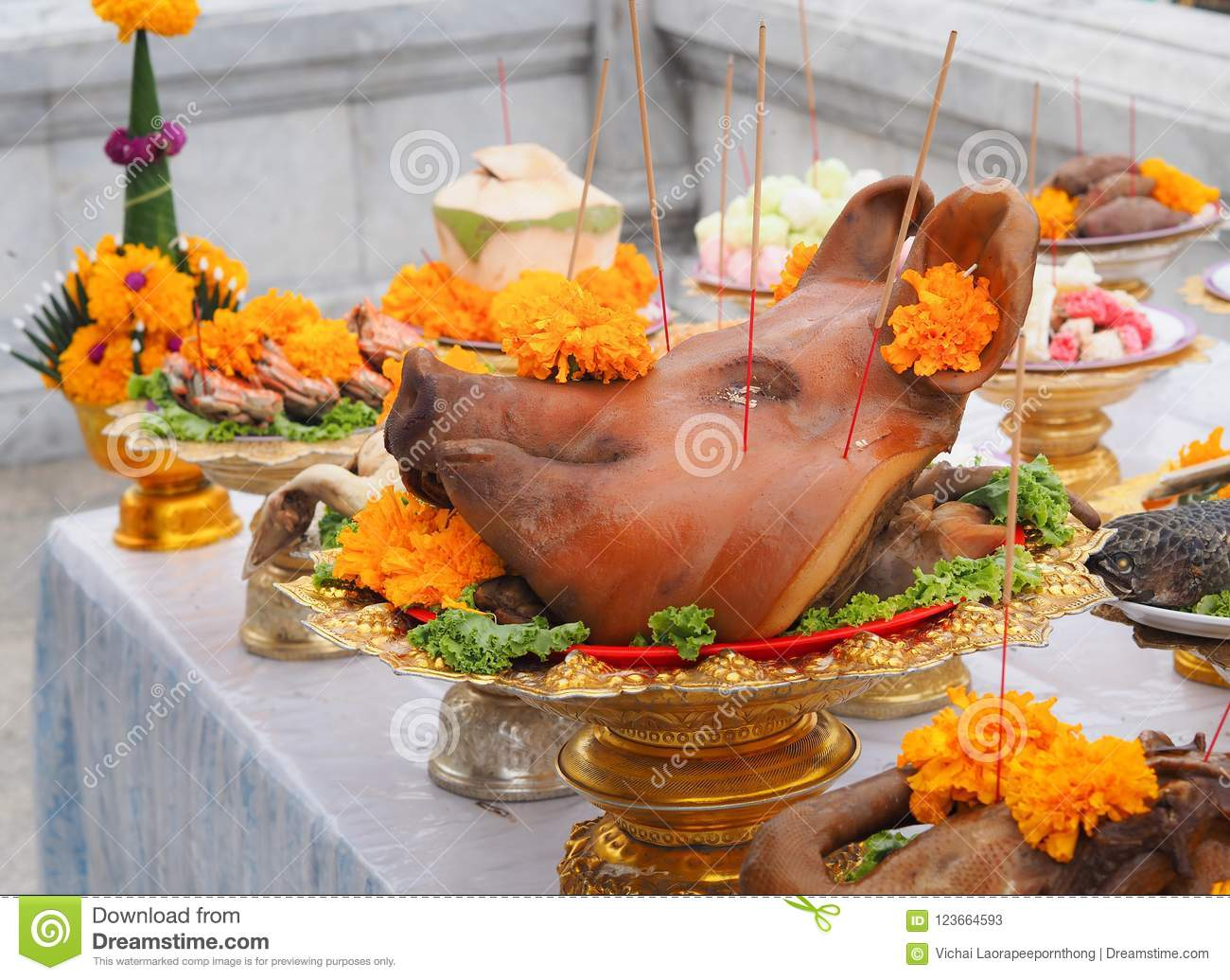 Boiled pig`s heads decorated with flowers sacrificial offering in worship.