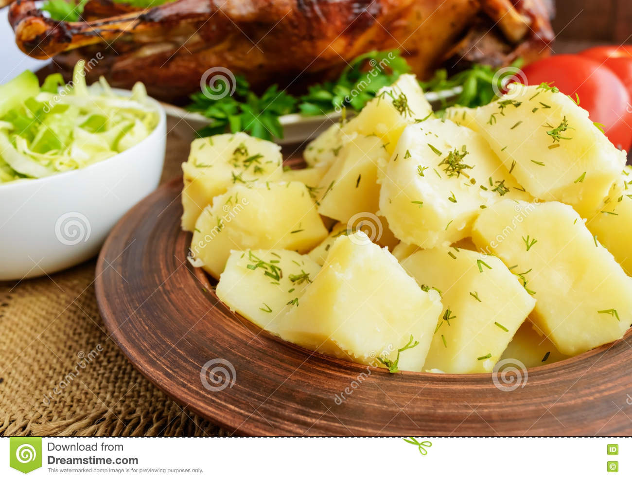 Boiled potatoes in a clay bowl and roasted goose.