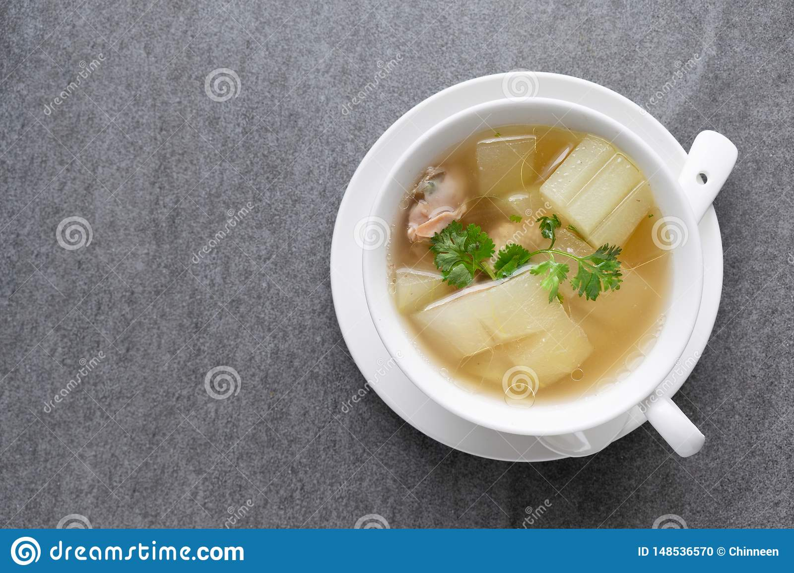 Boiled winter melon soup with chicken rib in white bowl on table
