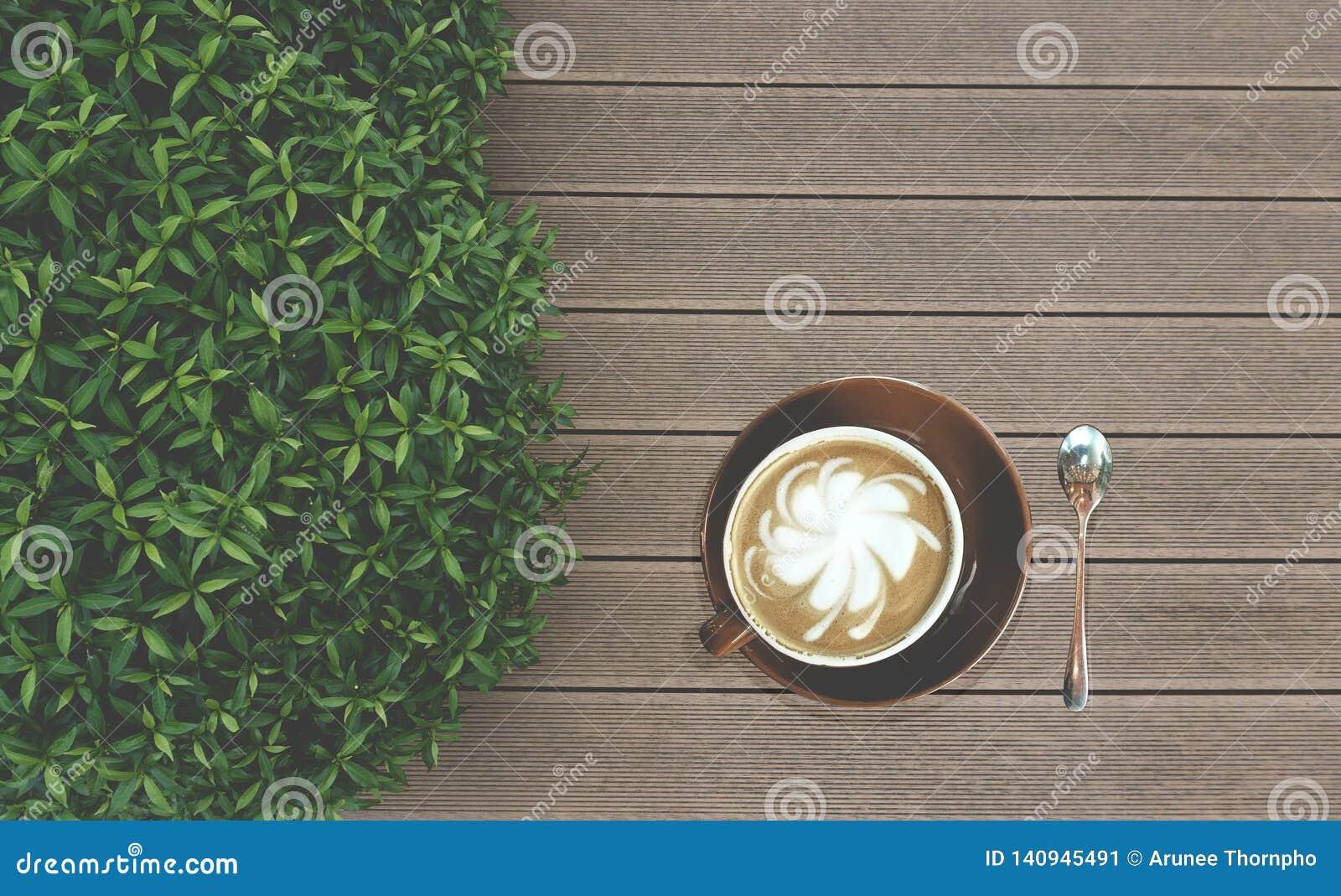 Boire savoureux, une tasse de café de cappuccino décorée du lait de modèle de fleur en avant dans la tasse en céramique brune et