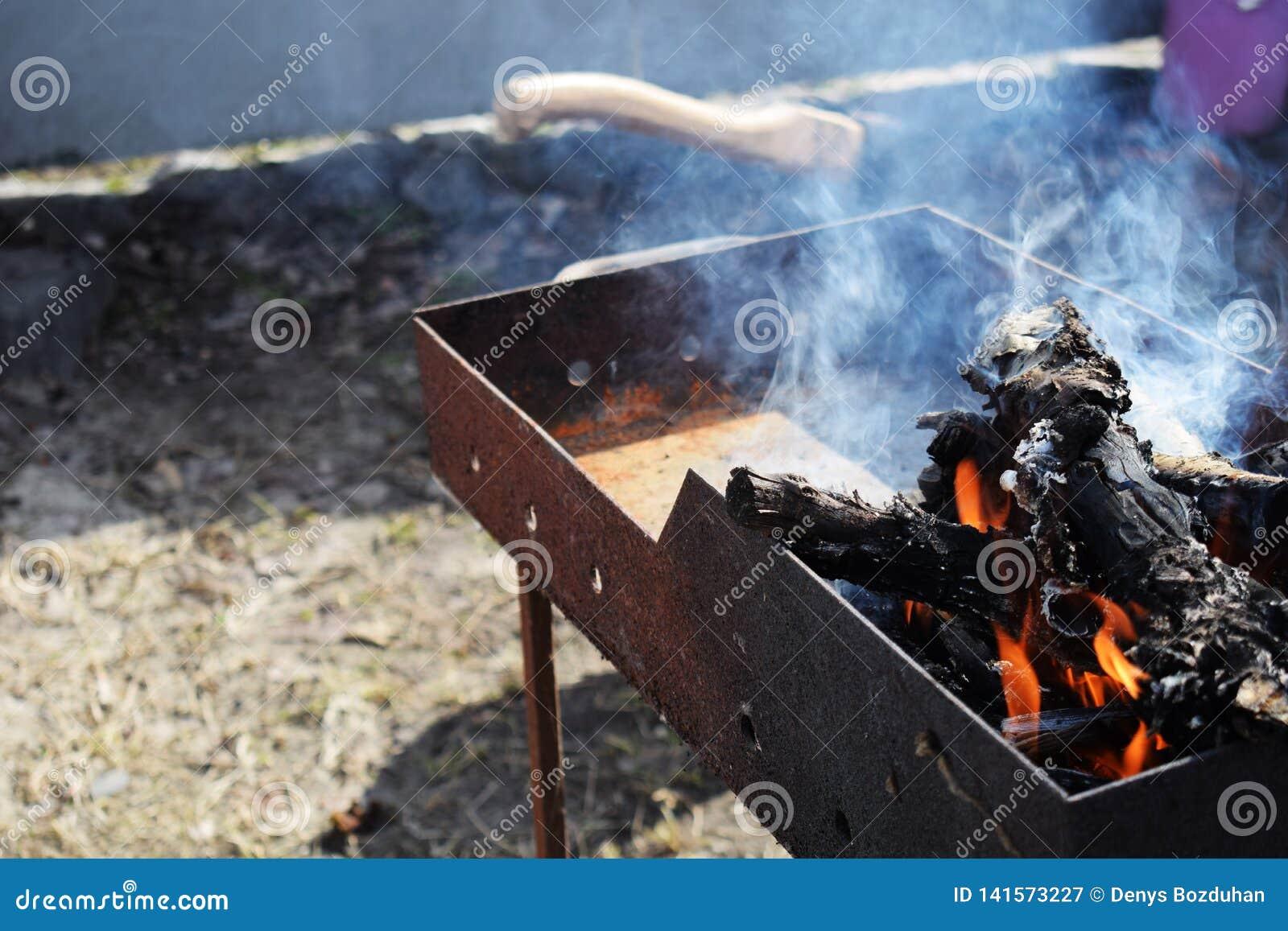 Bois de chauffage brûlant dans le vieux gril de gril, faisant cuire des chiches-kebabs