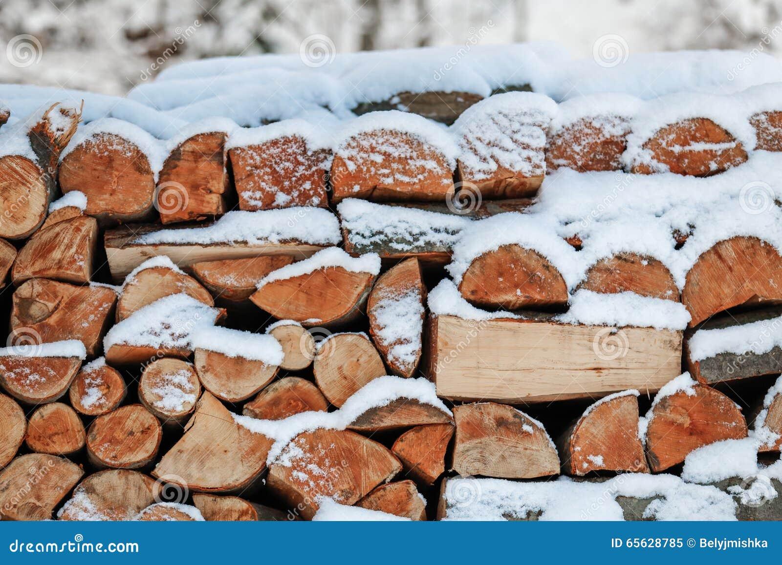 Bois de chauffage empilé et couvert de neige