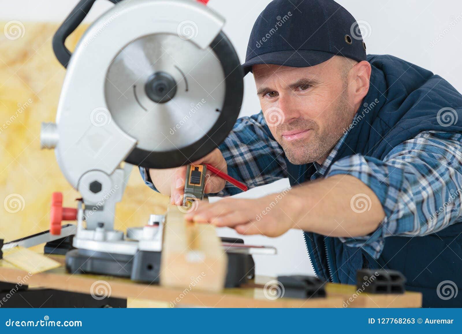 Bois de mesure de charpentier à couper avec la scie circulaire