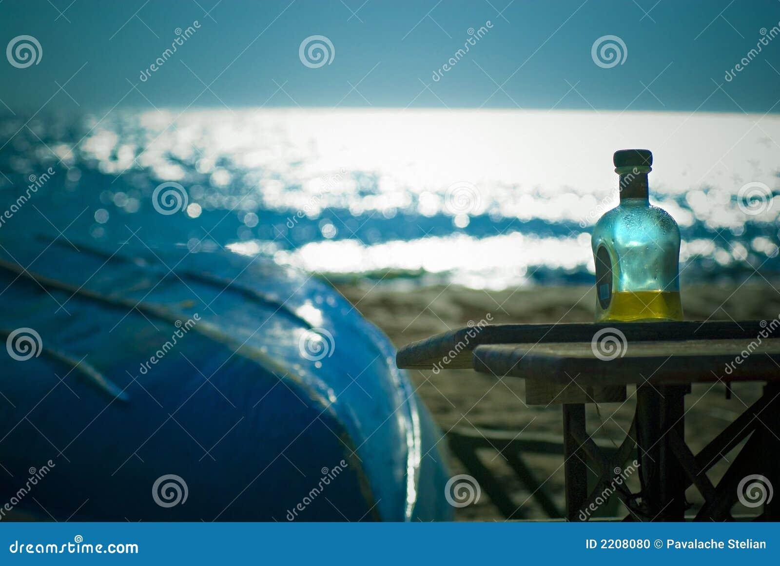 Boisson alcoolisée dure et bateau sur la plage