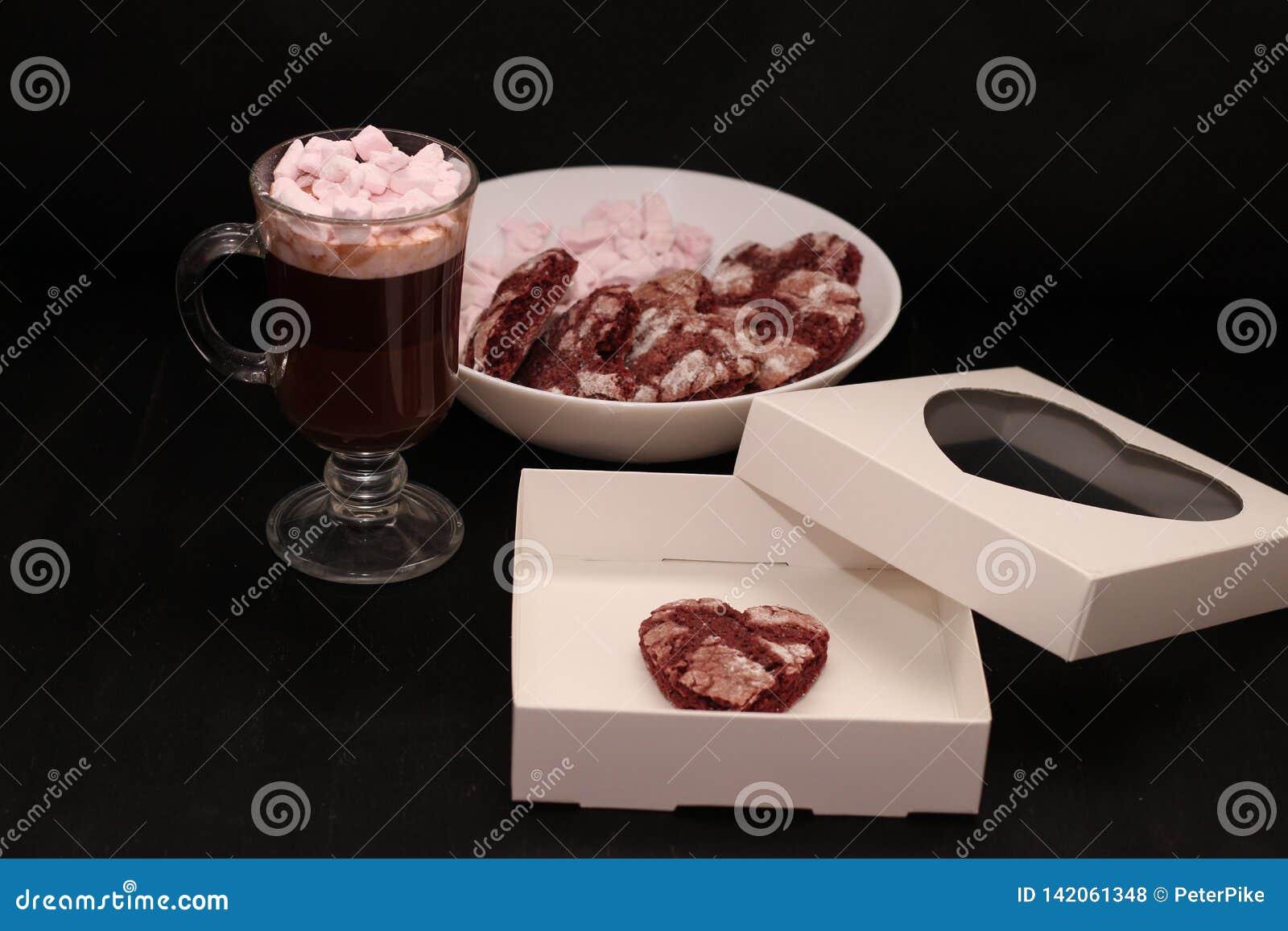 Boisson chaude dans une tasse en verre avec les guimauves et le boîtier blanc roses avec une couverture transparente sous forme d