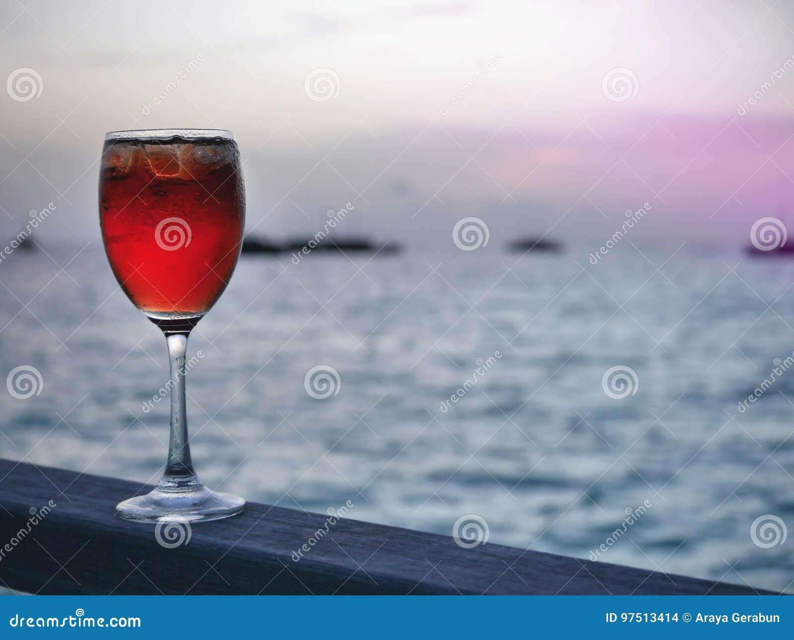 Boisson froide glacée rouge en verre de vin sur le morceau en bois avec le fond de coucher du soleil des bateaux de mer ouverte e