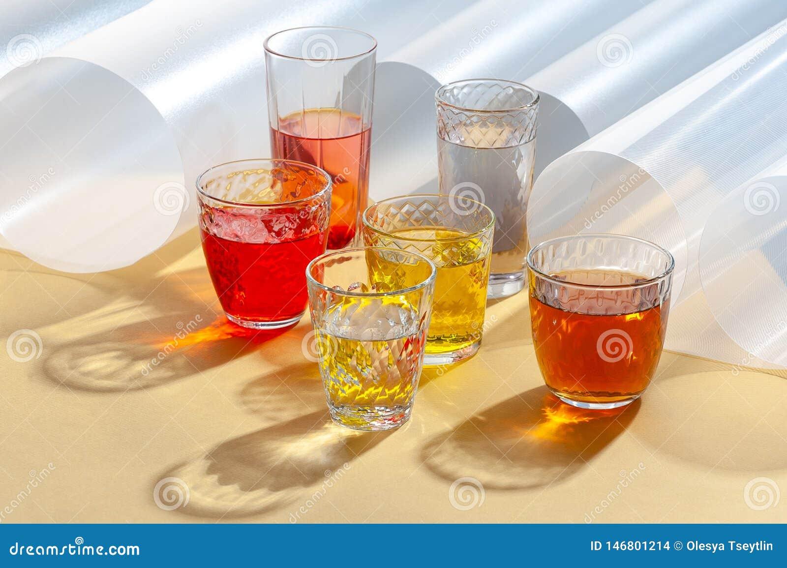 Boissons colorées dans des tasses en verre sur un fond jaune avec les éléments complémentaires