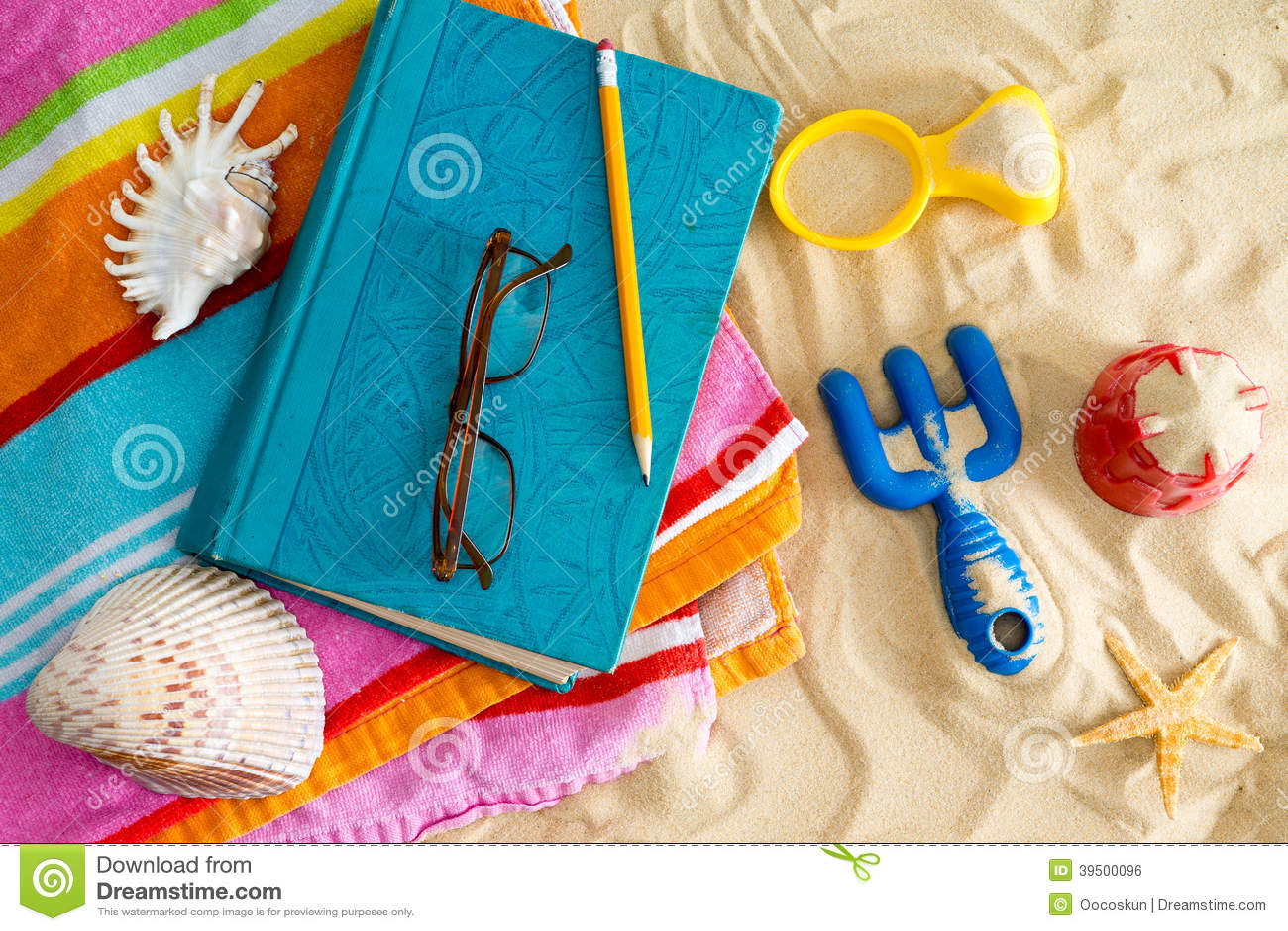Bok och läs- exponeringsglas på en strandhandduk