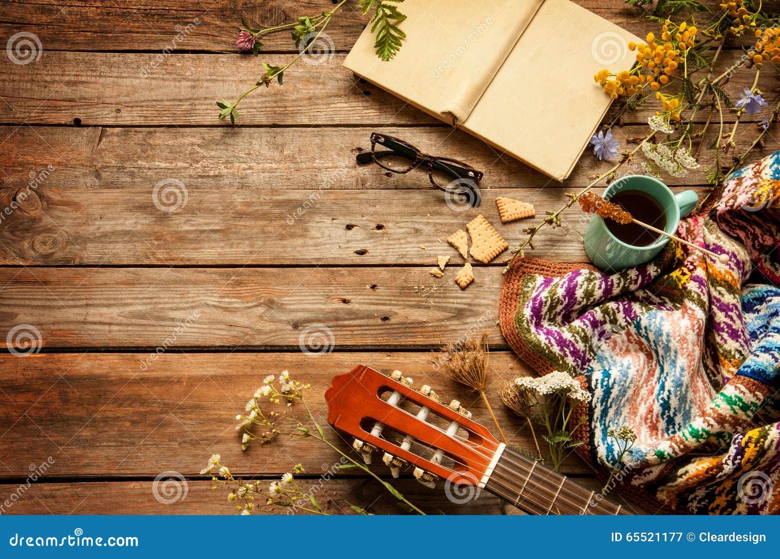 Boka, filt, kaffe- och klassikergitarren på trä