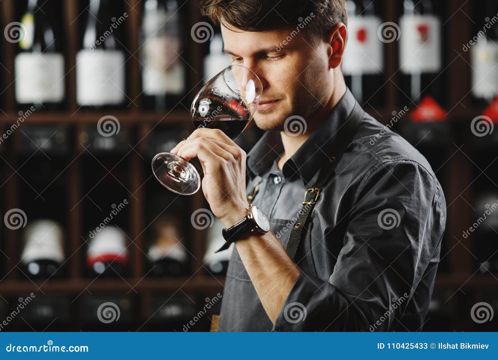 Bokal czerwone wino na tle, męski sommelier docenia napój