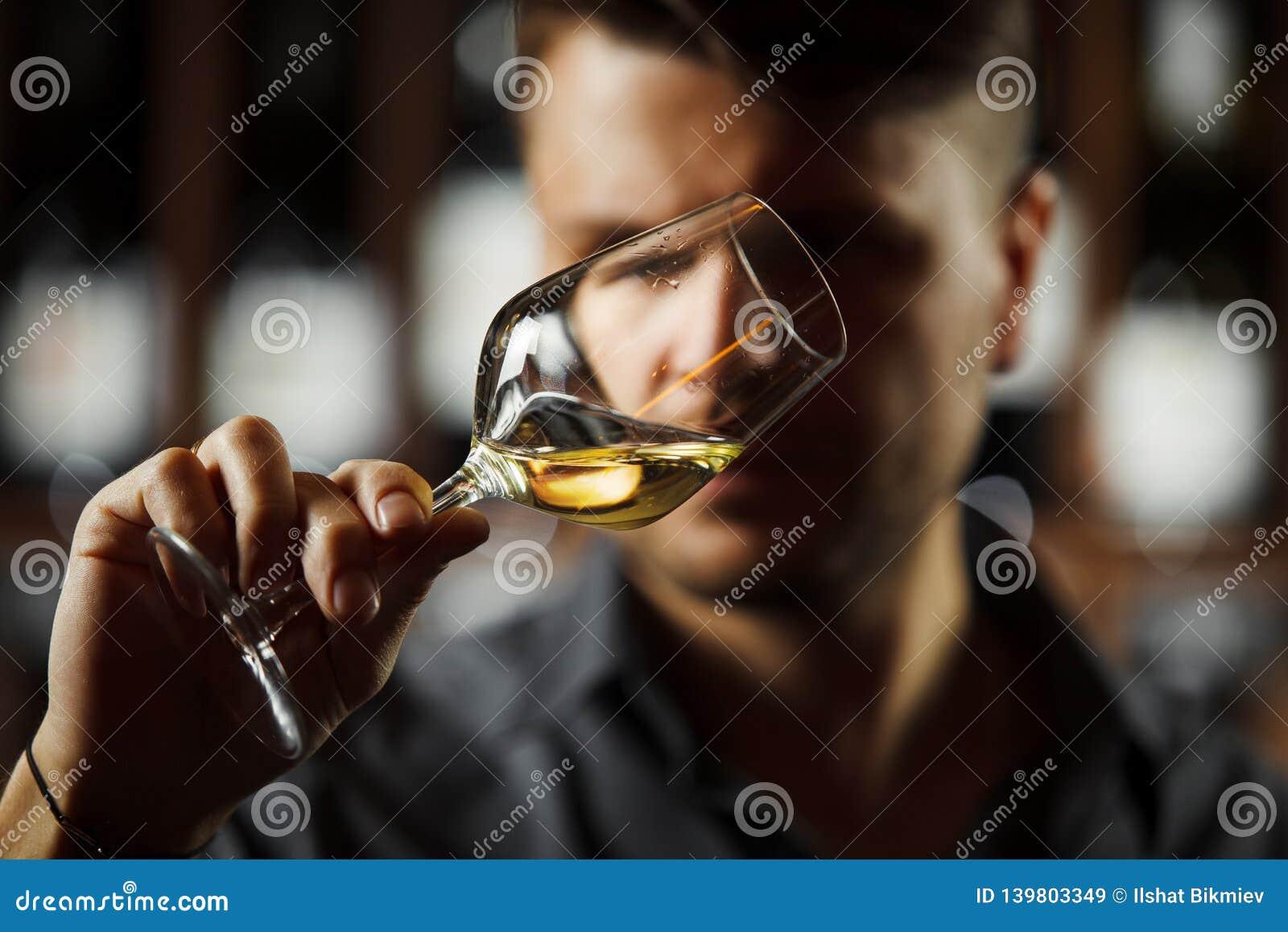 Bokal del vino blanco en el fondo, sommelier masculino que aprecia la bebida